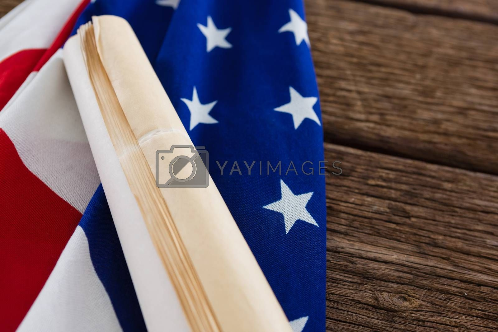 American flag with rolled-up of constitution document on wooden table