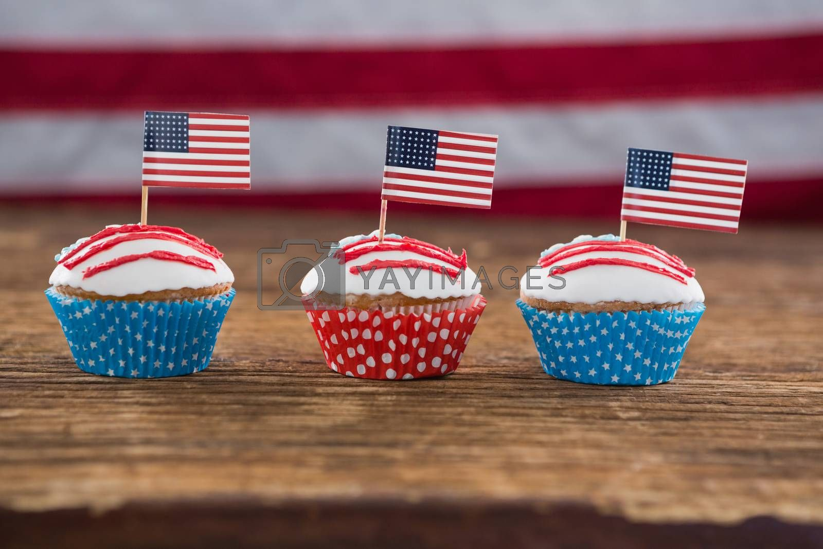 Close-up of patriotic cupcake with American flag on wooden table