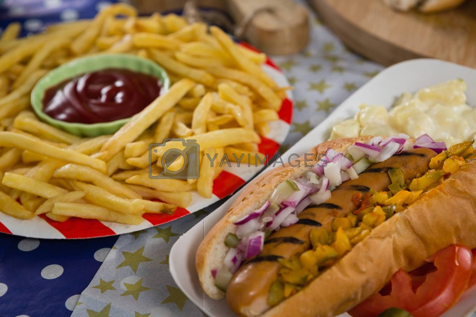 Close-up of hot dog and french fries on wooden table with 4th july theme