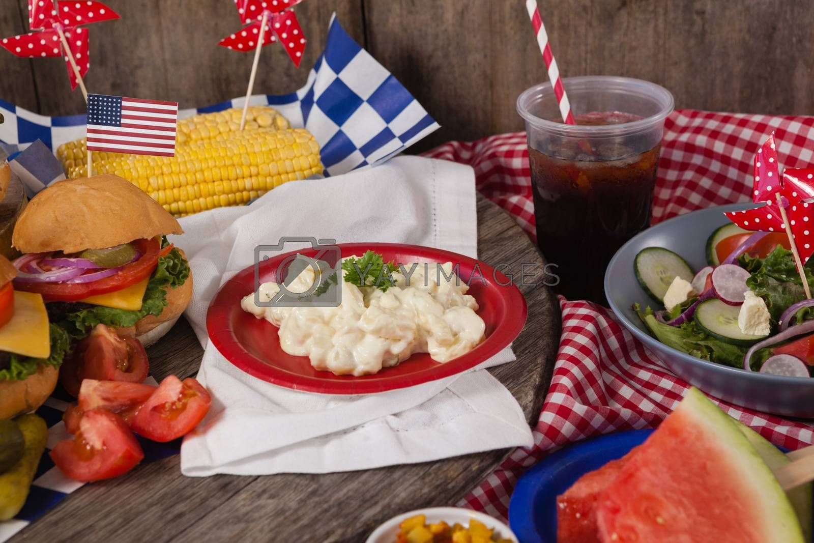 Snacks and cold drink decorated with 4th july theme on wooden table