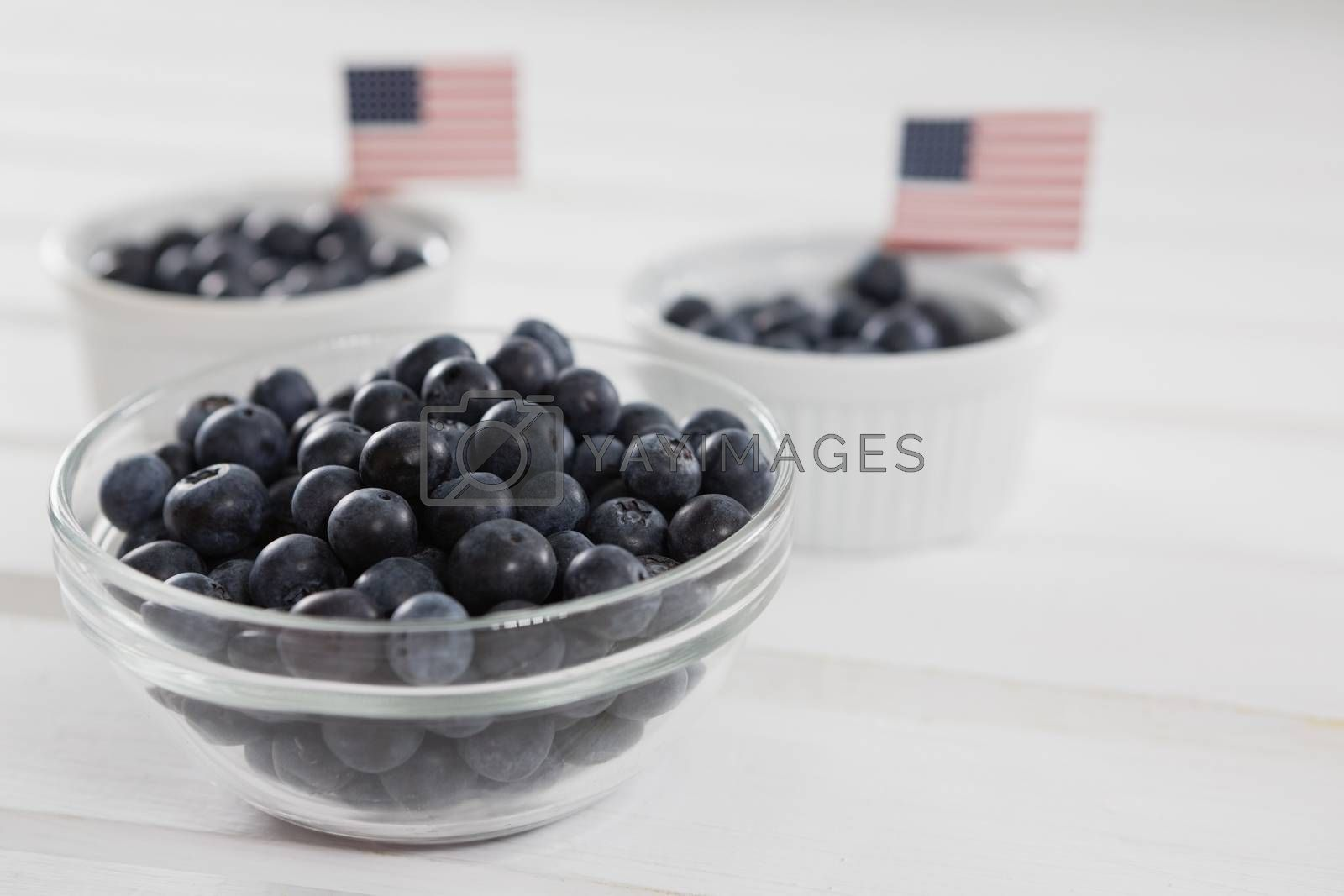 Black berries in bowls with 4th july theme on wooden table