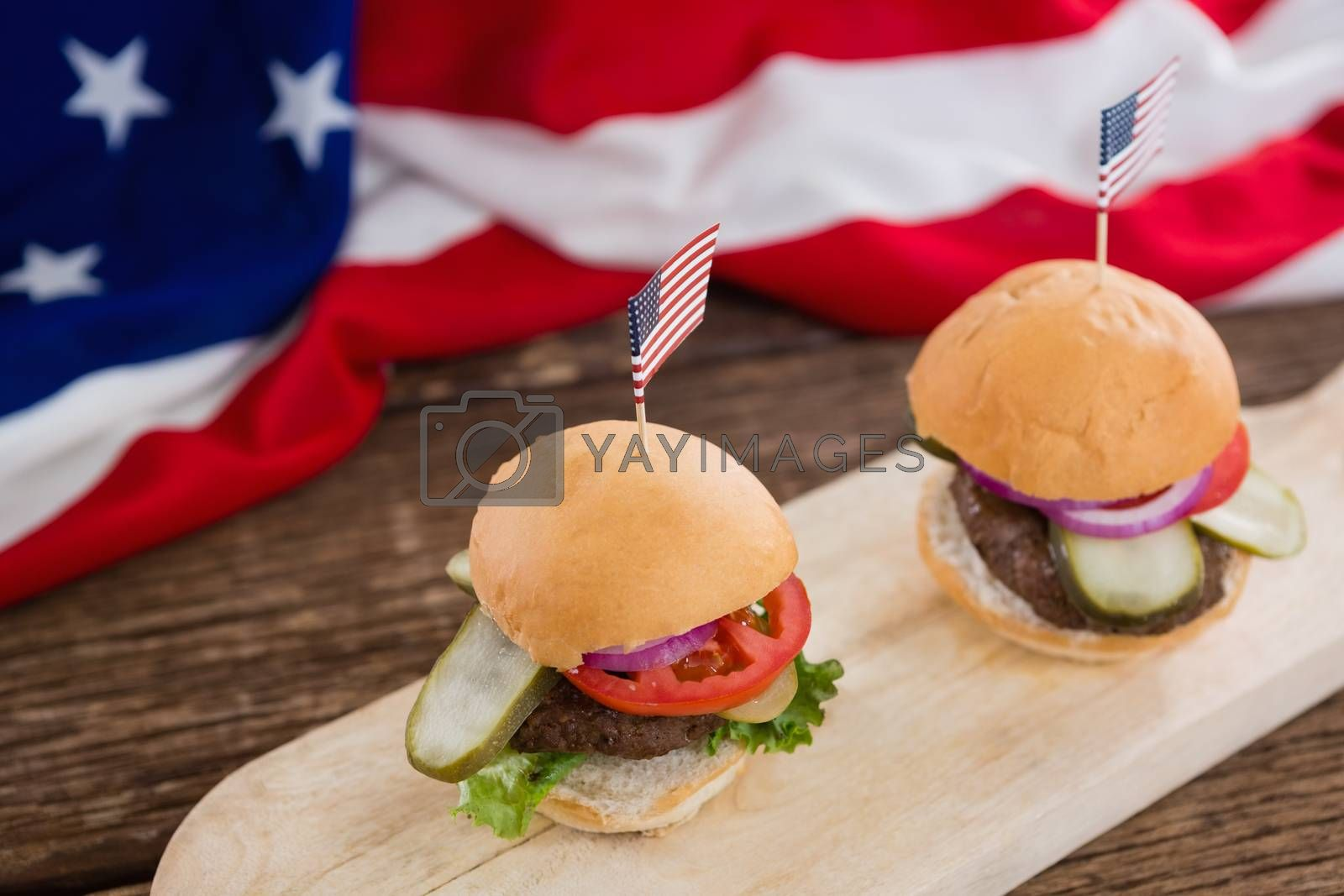 Burgers arranged on wooden board with 4th july theme