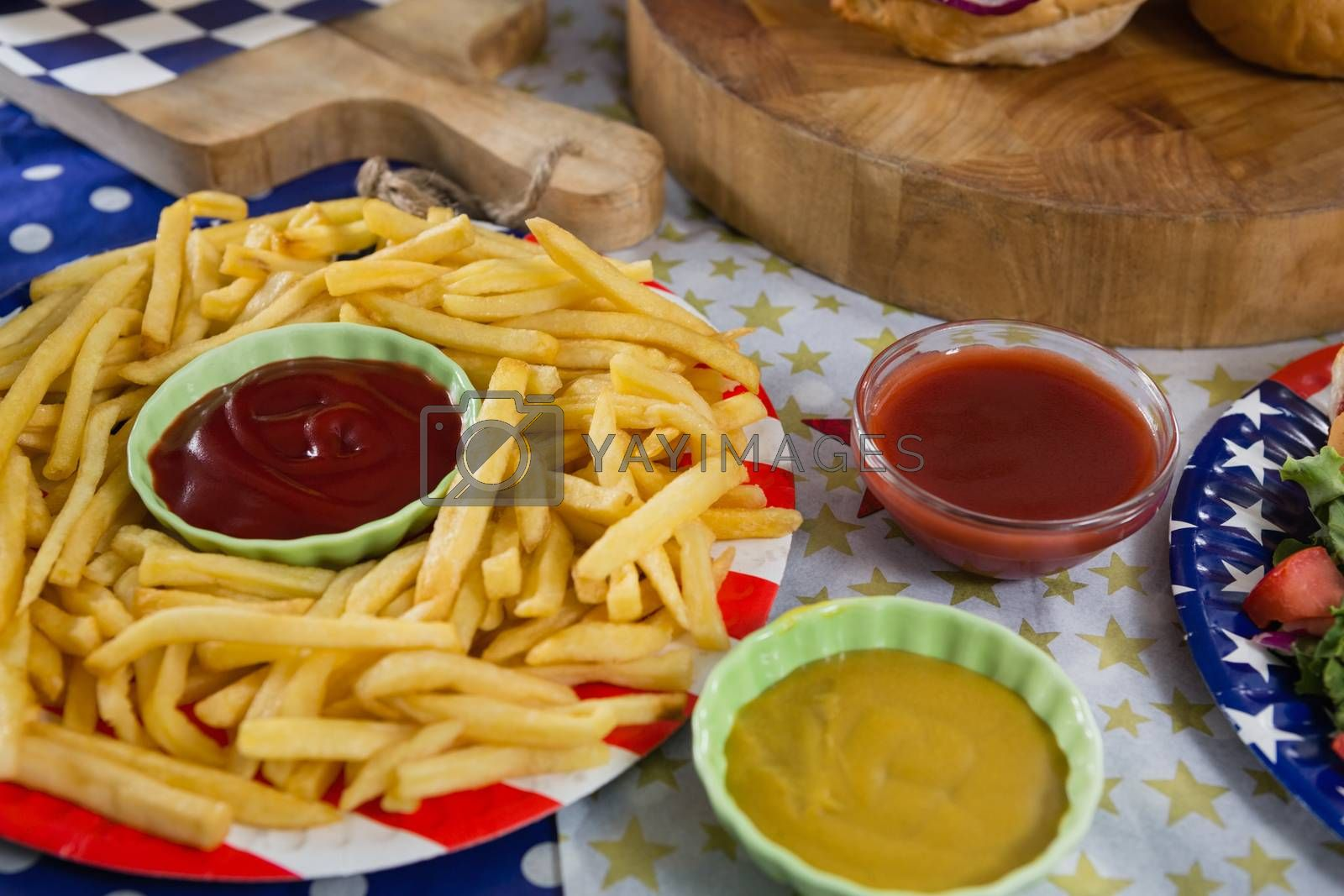 Close-up of french fries on wooden table with 4th july theme
