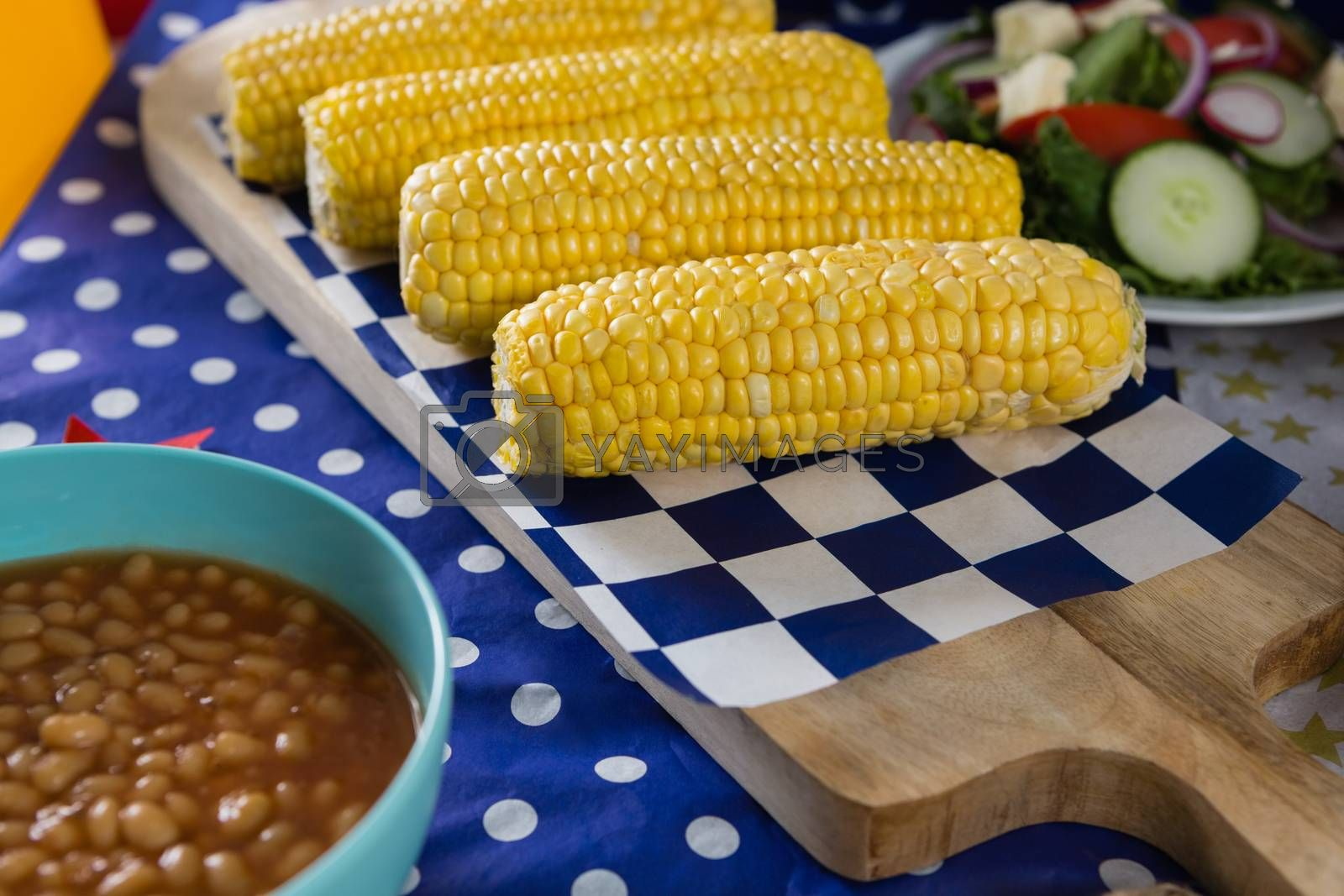 Royalty free image of Baked beans and corn cob on wooden table with 4th july theme by Wavebreakmedia