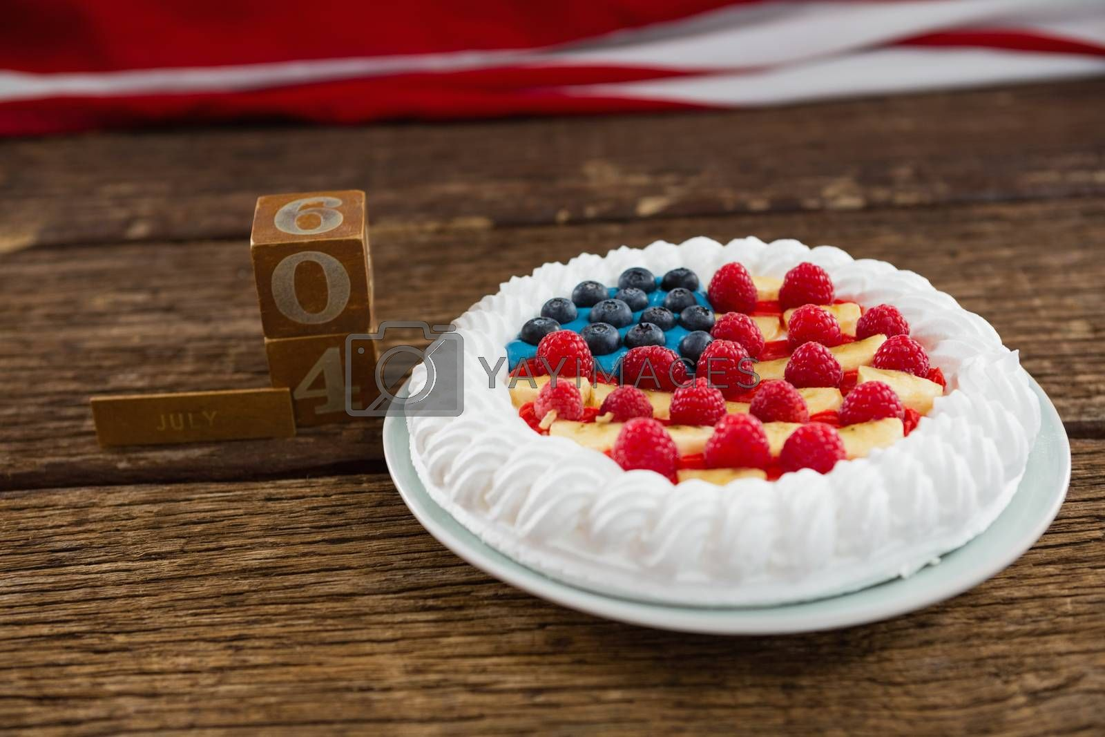 Close-up of date blocks and fruitcake on wooden table with 4th july theme