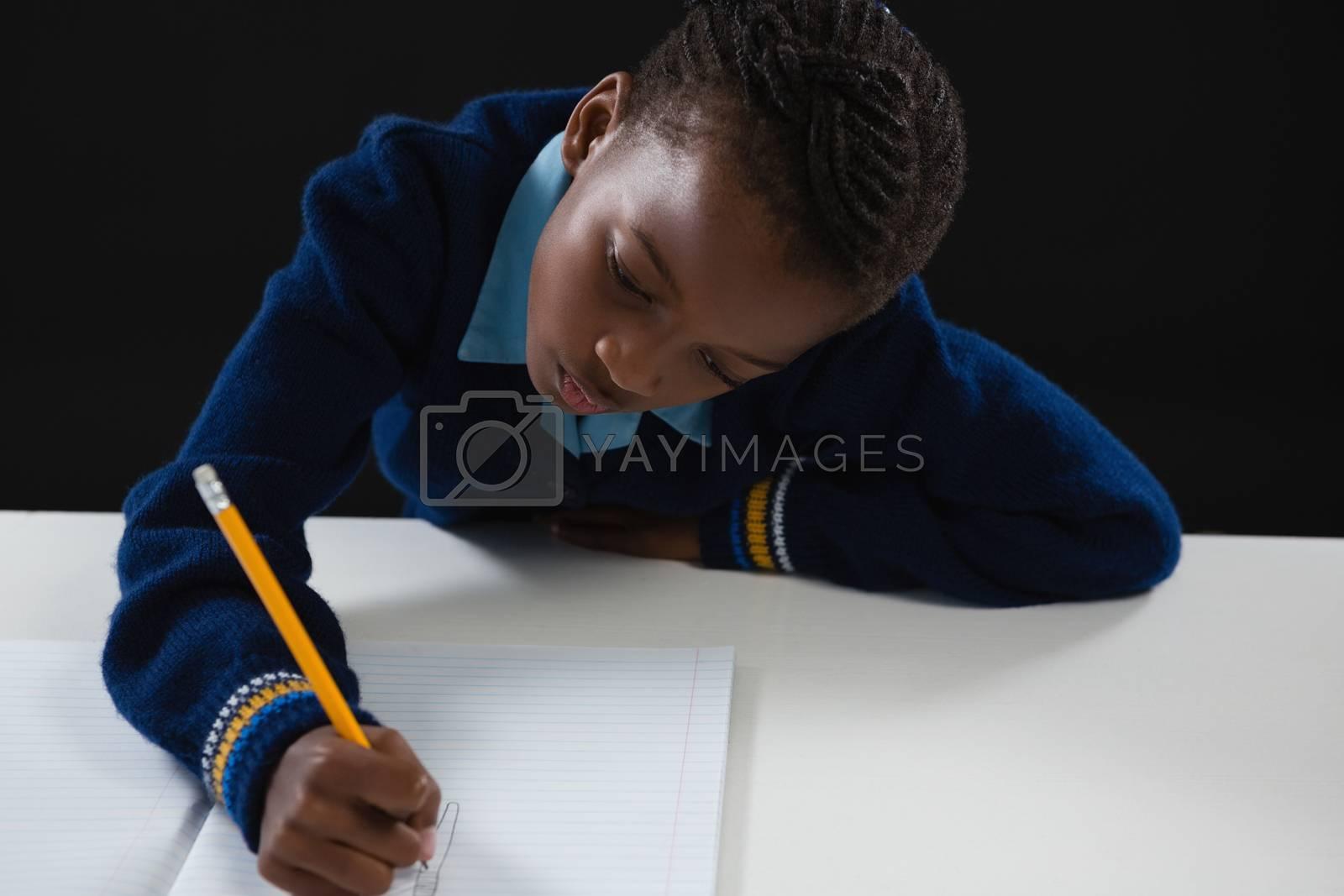 Schoolgirl doing his homework against black background by Wavebreakmedia
