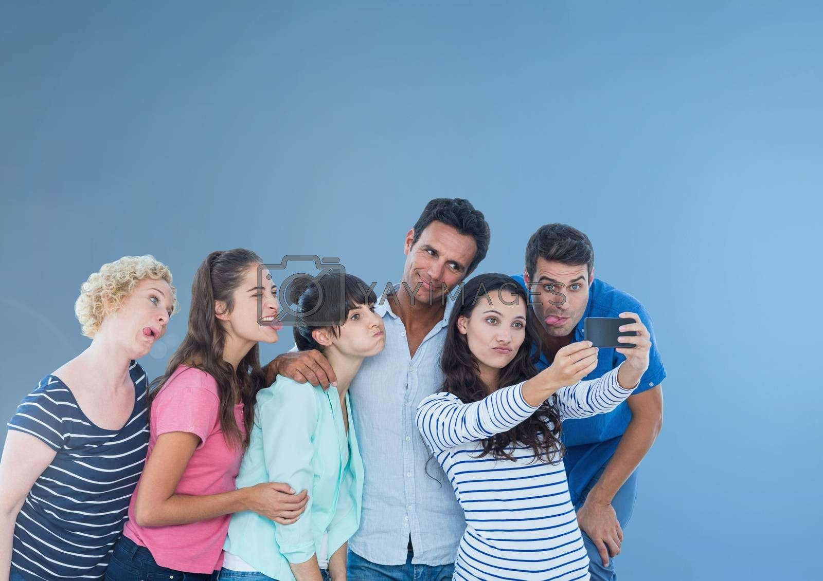 Group of people taking a funny silly selfie in front of blue background by Wavebreakmedia