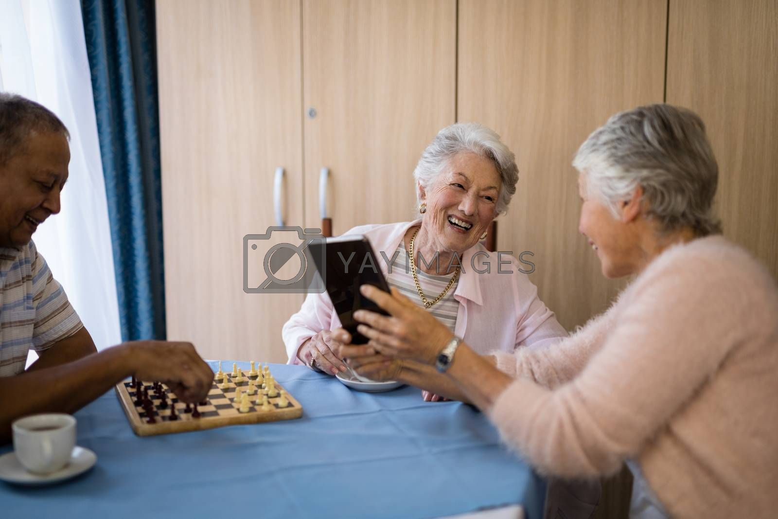 Smiling senior friends playing chess and using technology while sitting at table in nursing home