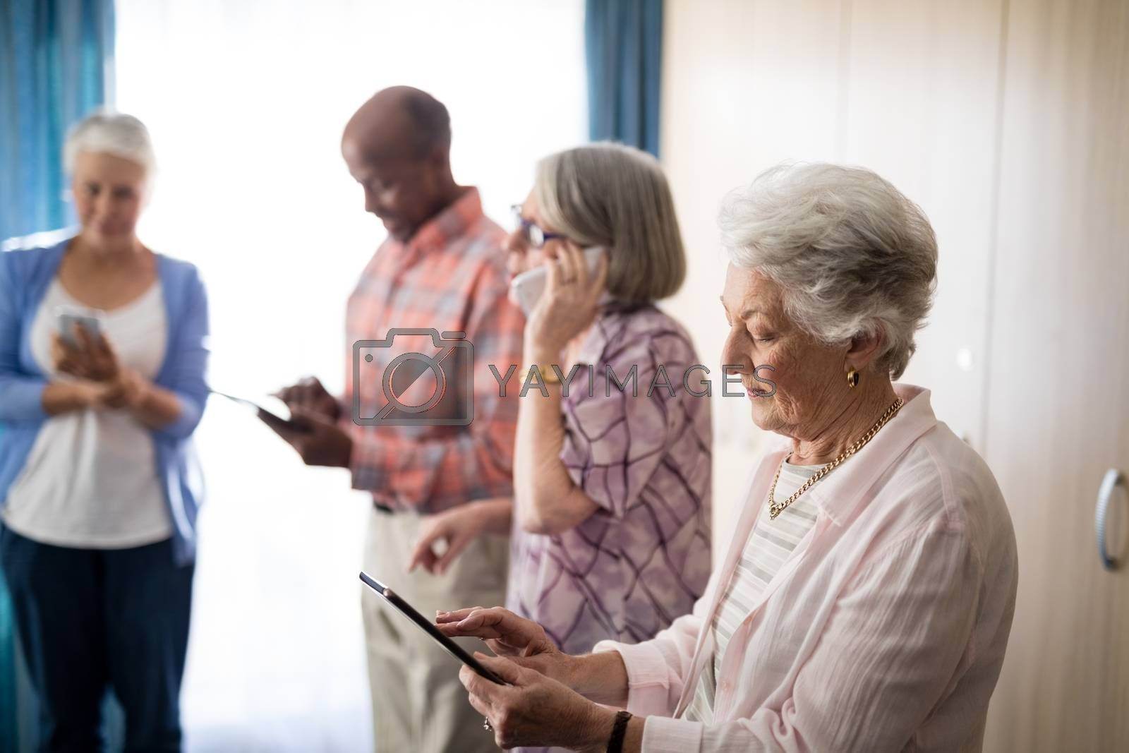 Seniors using technologies while standing against window at retirement home