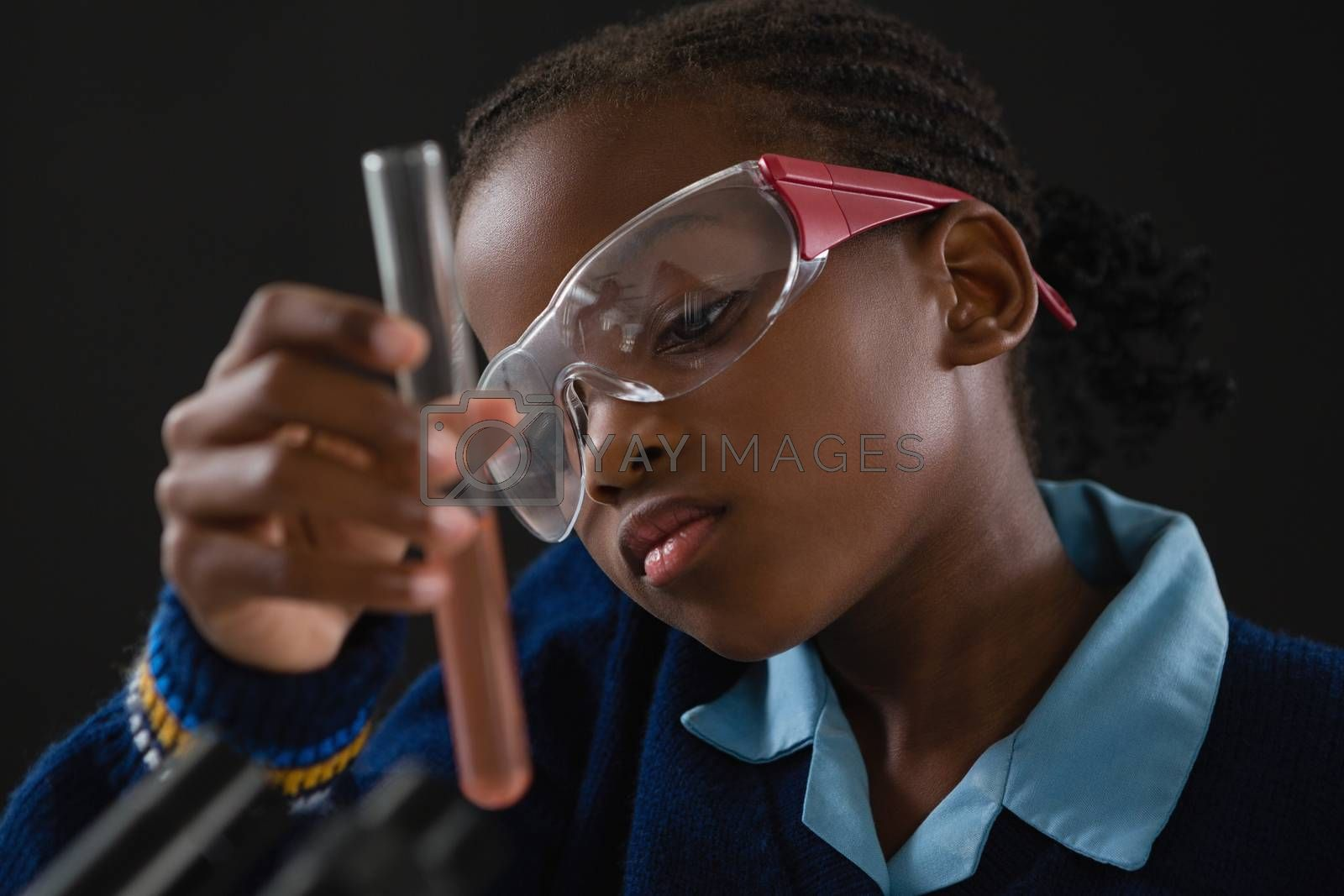 Attentive schoolgirl doing a chemical experiment against black background