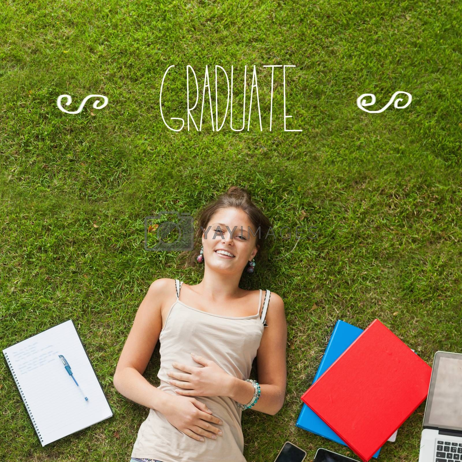 The word graduate against pretty student lying on grass