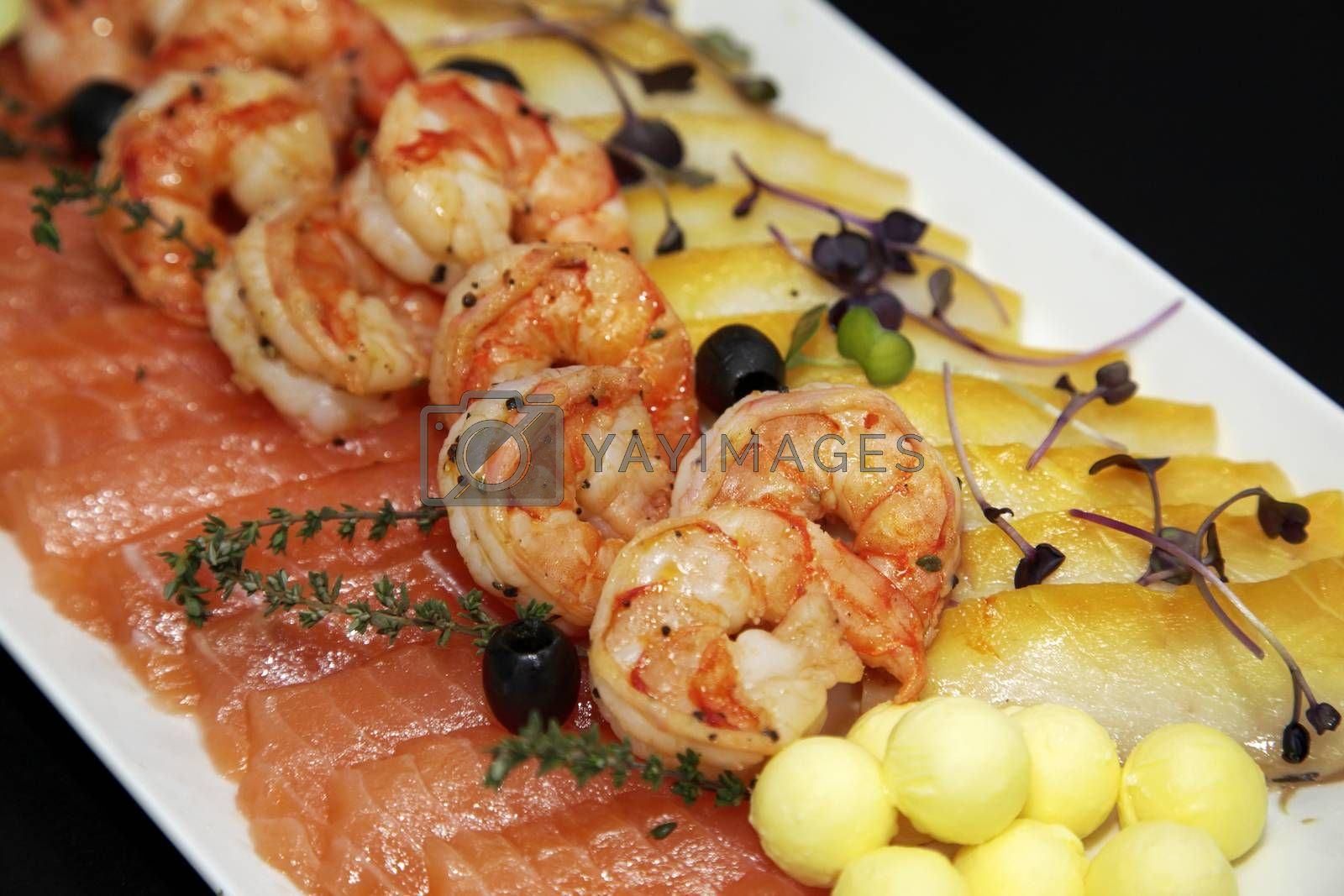 Assorted shrimp, trout and oily fish with balls of oil and black olives