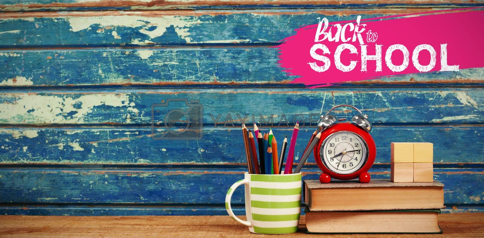 back to school against books with alarm clock on table