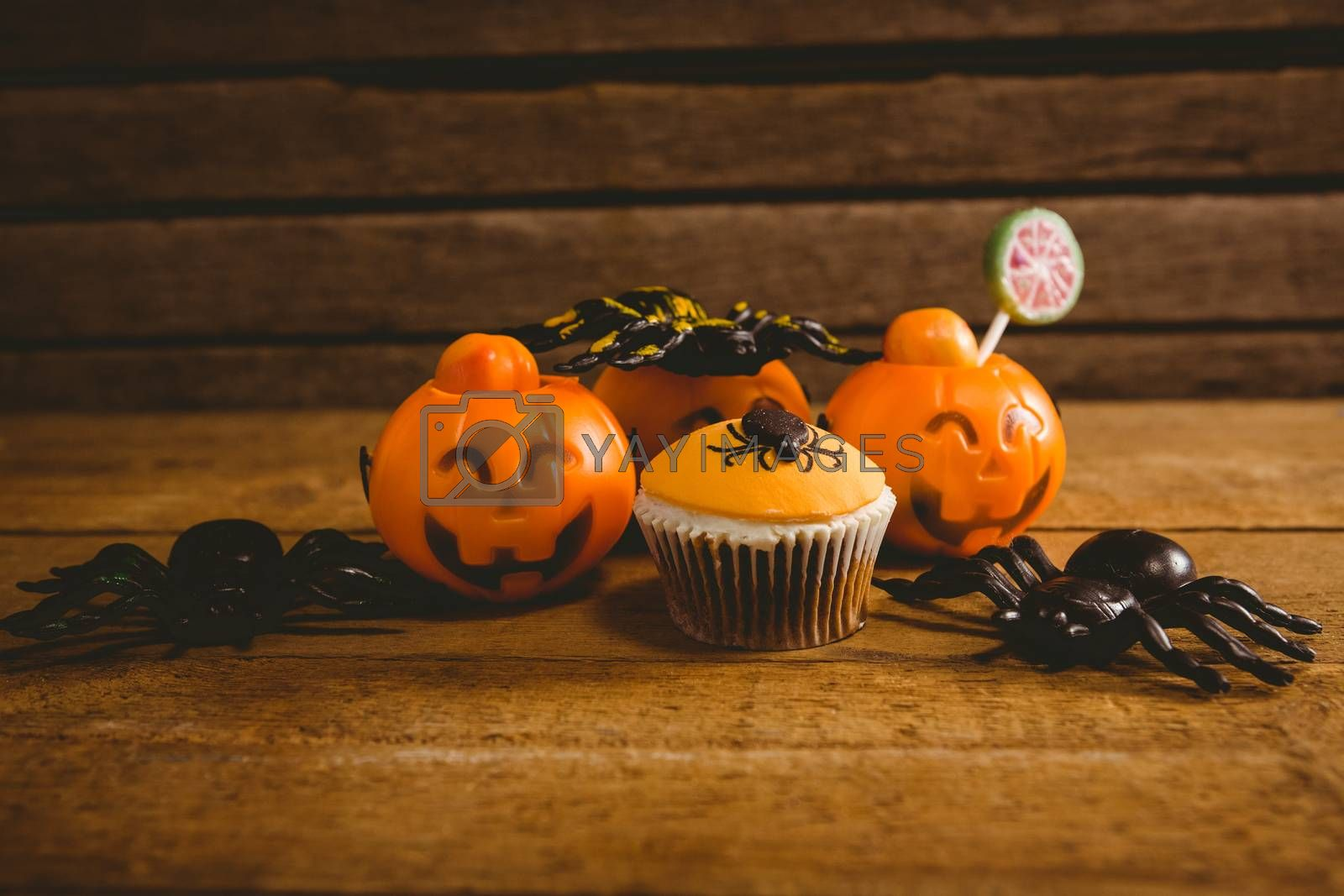 Halloween decorations with cup cake on wooden table