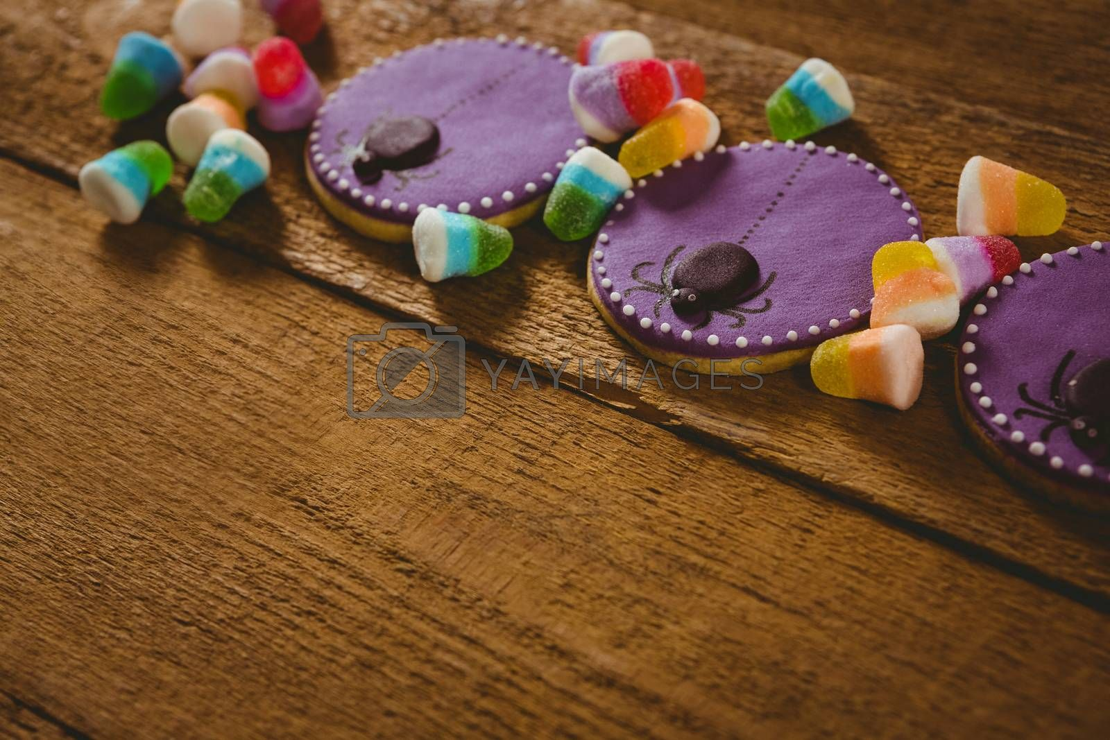 Close up of Halloween cookies with candies on wooden table