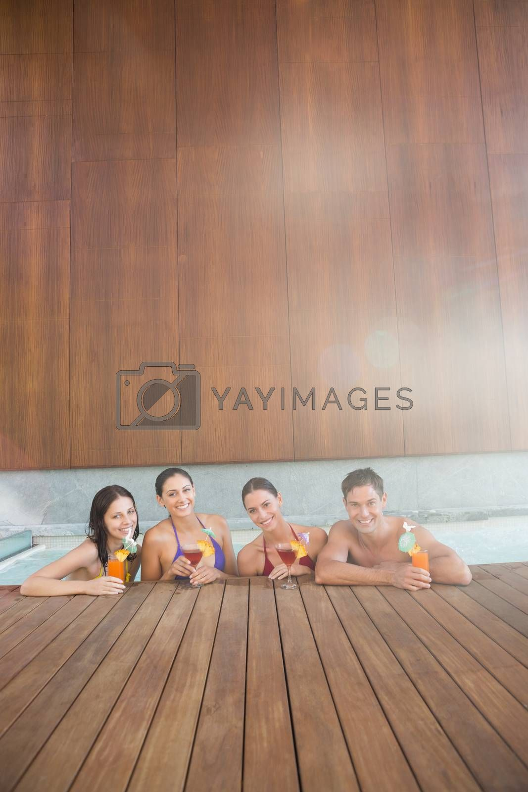 Portrait of cheerful young people with drinks in the swimming pool