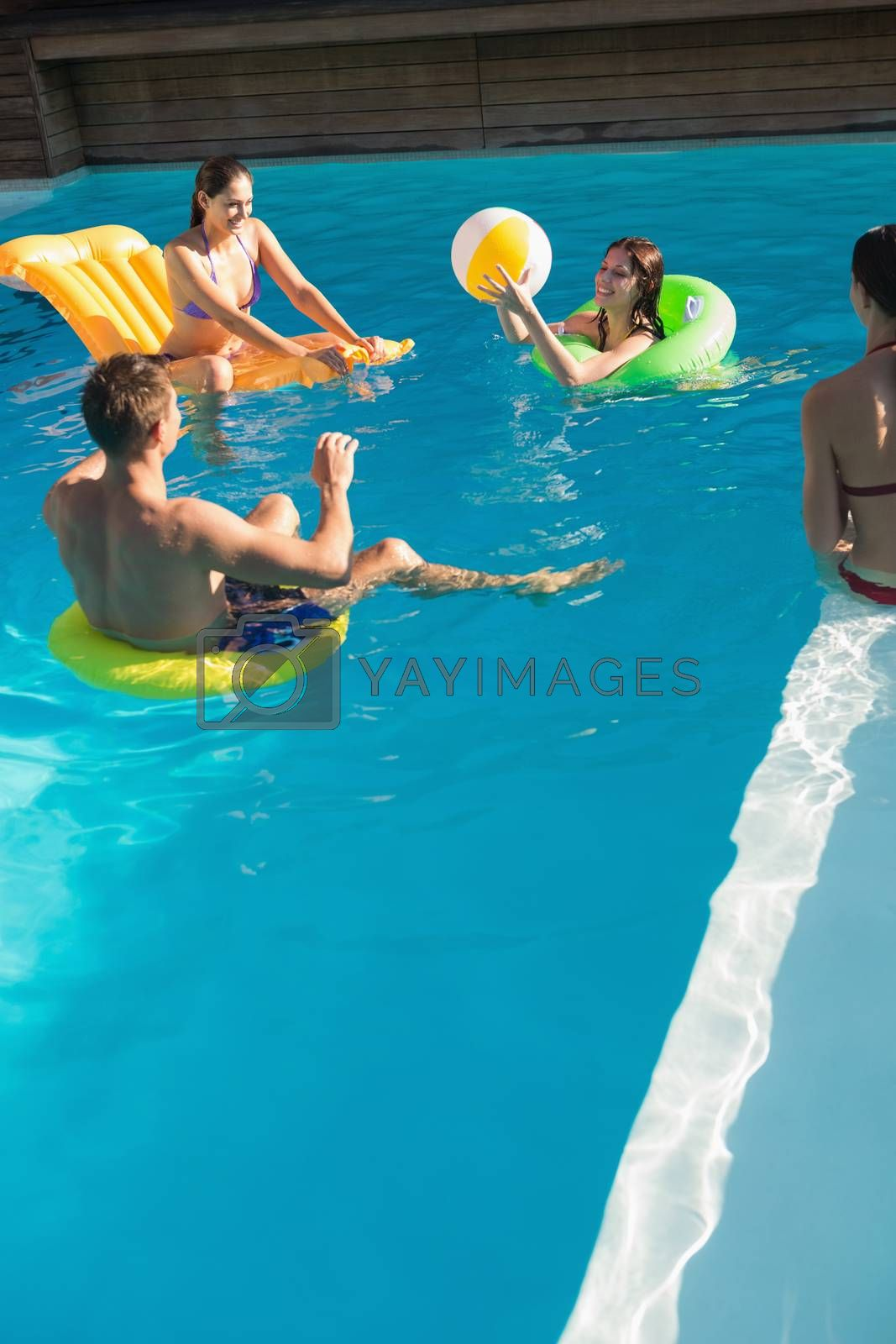 Cheerful young people playing with ball in swimming pool