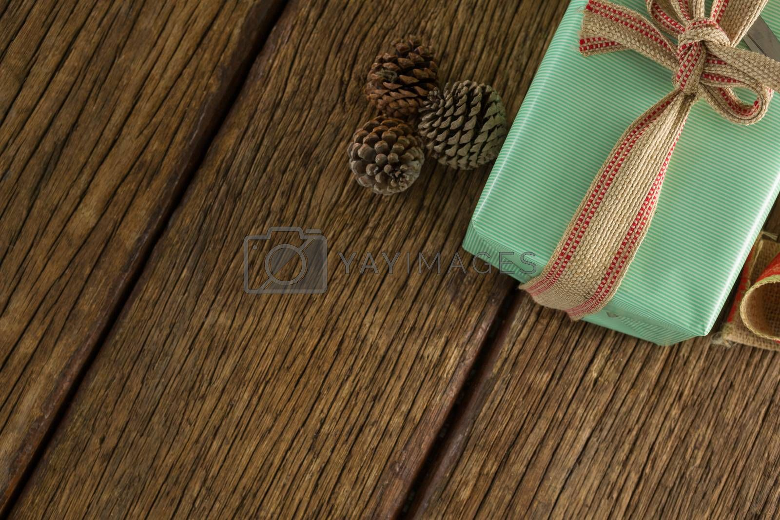 Pine cones and wrapped gift box on wooden table by Wavebreakmedia