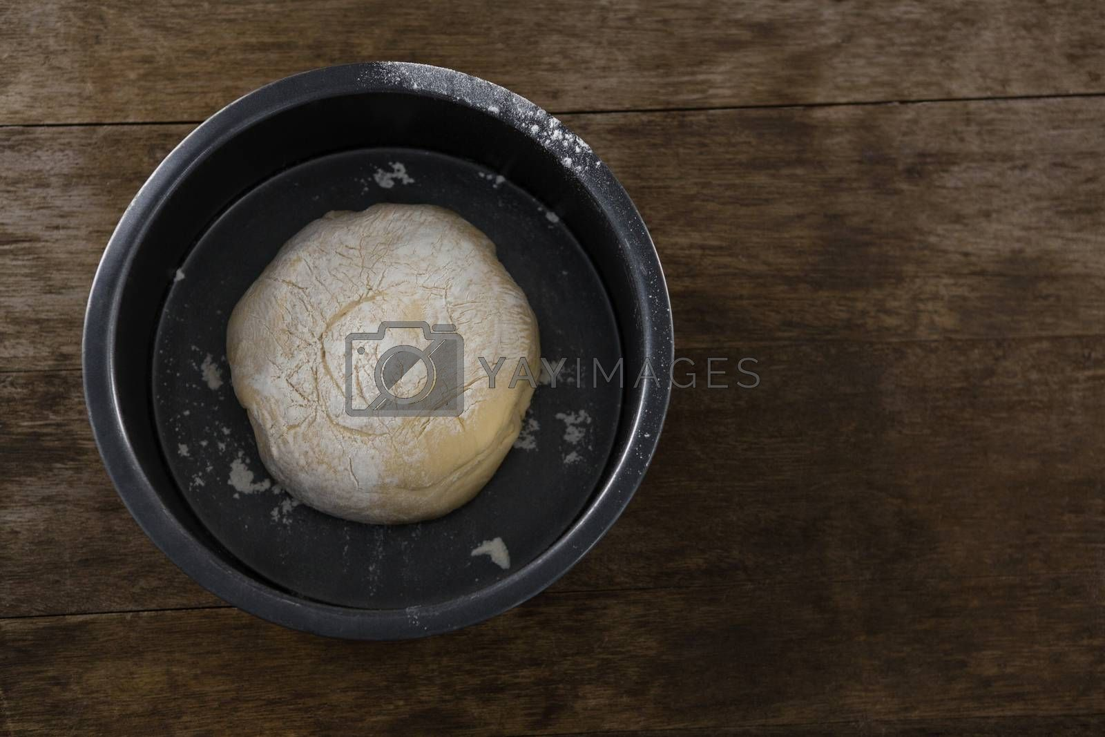 Kneaded dough placed in a bowl on a wooden table by Wavebreakmedia