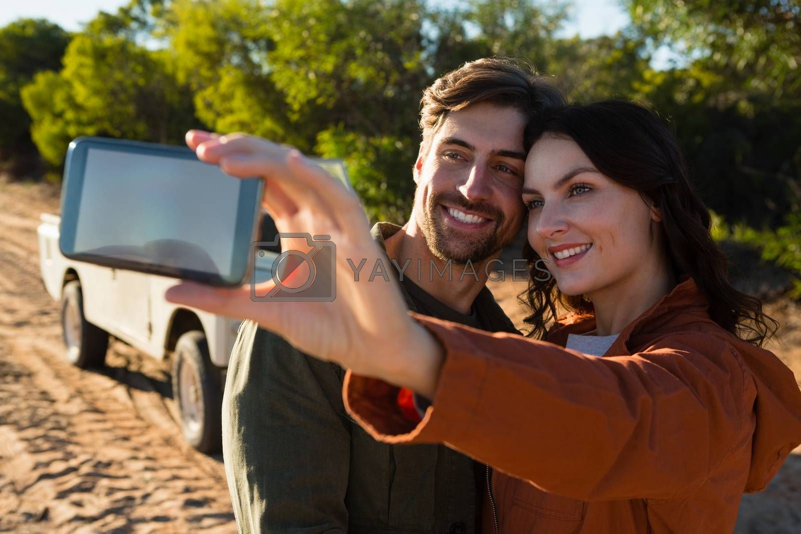 Young woman with man taking selfie on field by Wavebreakmedia
