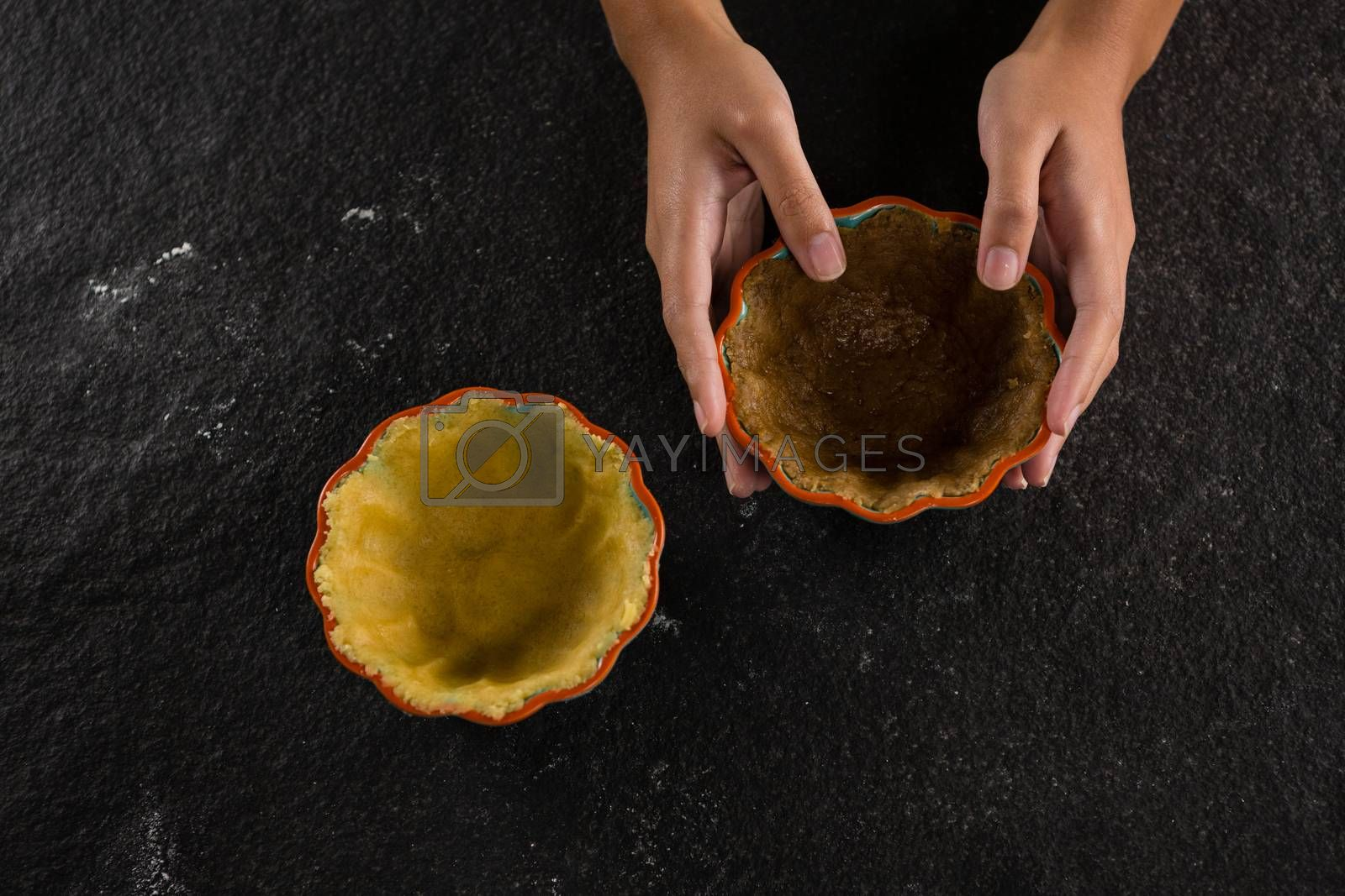 Woman holding tart dough on mold by Wavebreakmedia