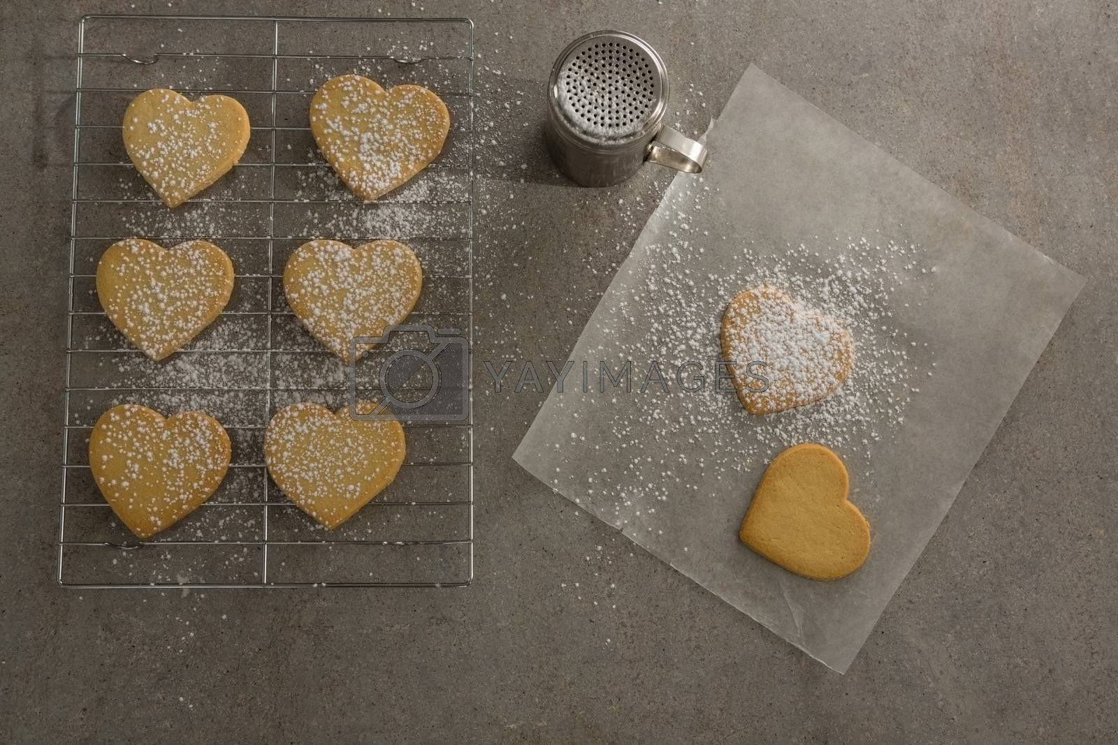 Raw heart shape cookies on baking tray with flour shaker strainer and wax paper by Wavebreakmedia