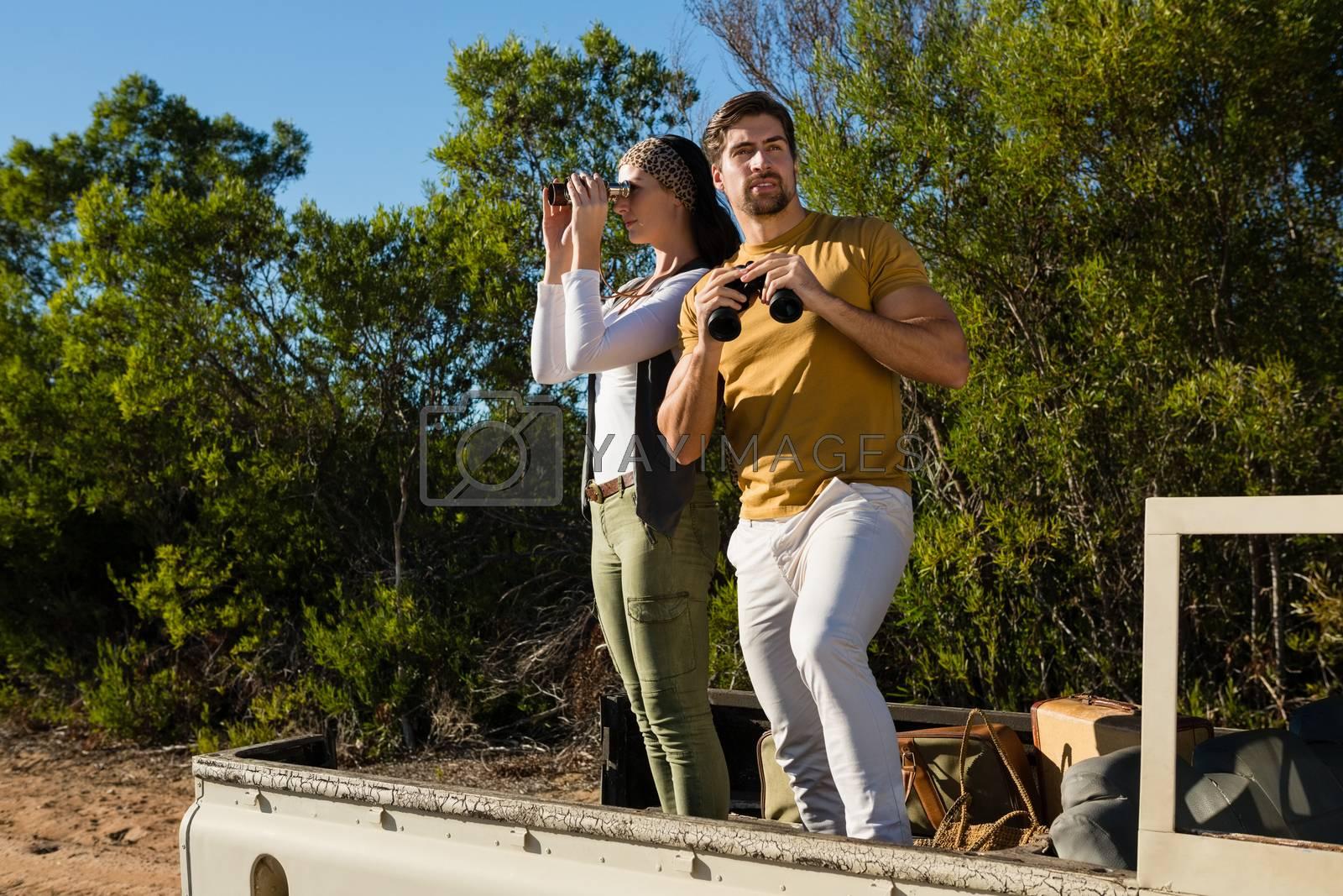 Couple looking through binoculars in off road vehicle by Wavebreakmedia