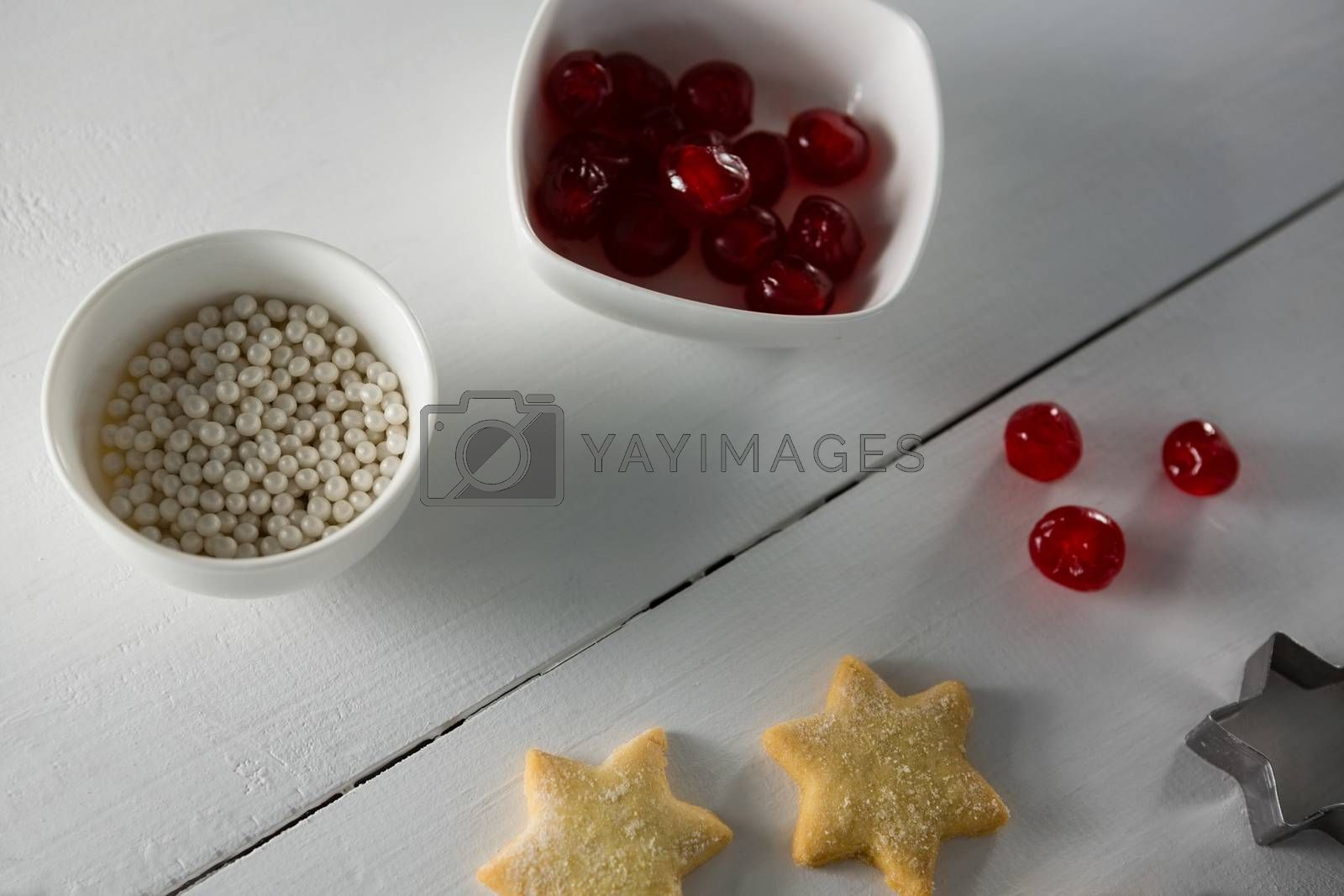 Red cherries in bowl with star shape cookies and cutter by Wavebreakmedia