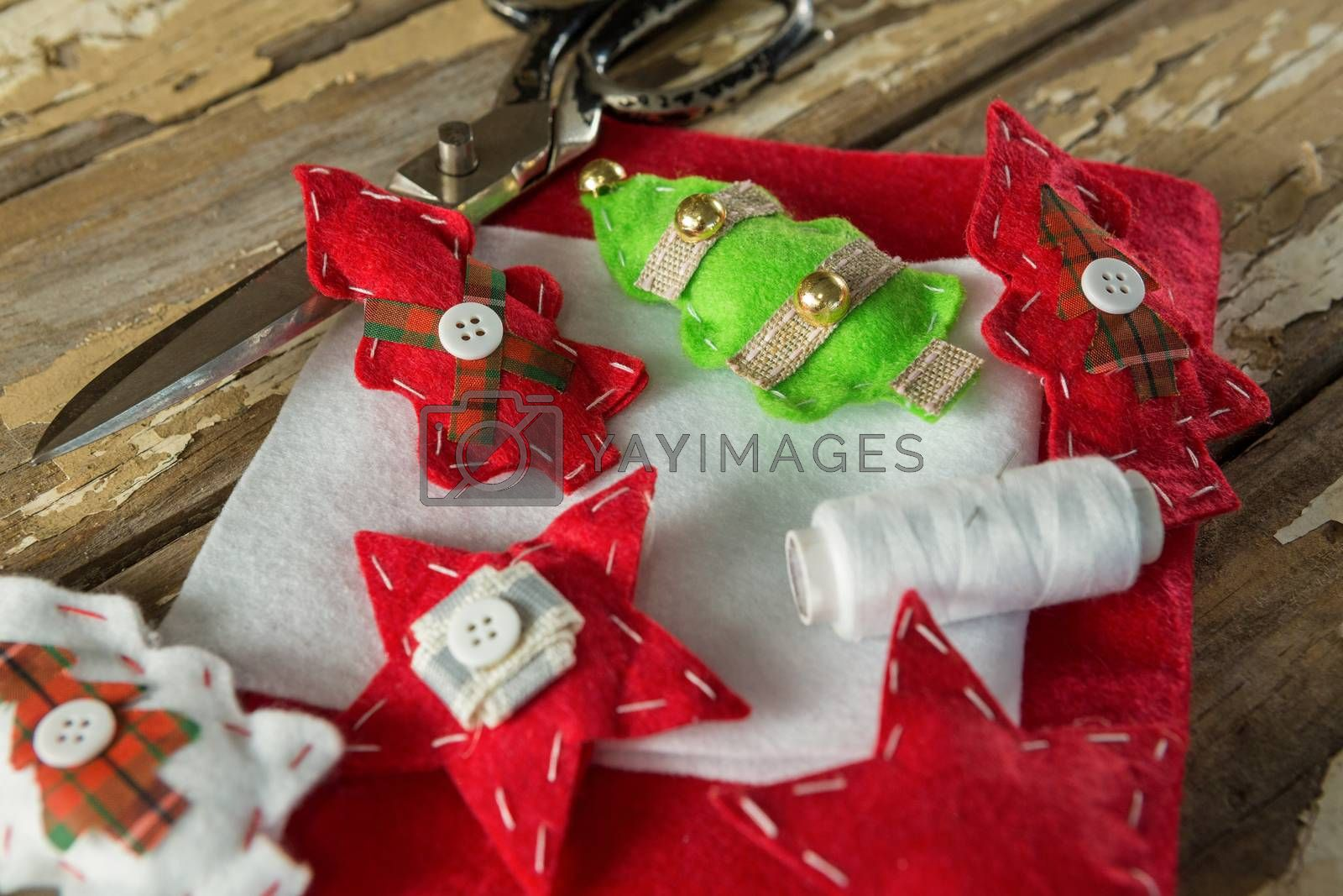 Handmade christmas trees and craft material on wooden plank by Wavebreakmedia