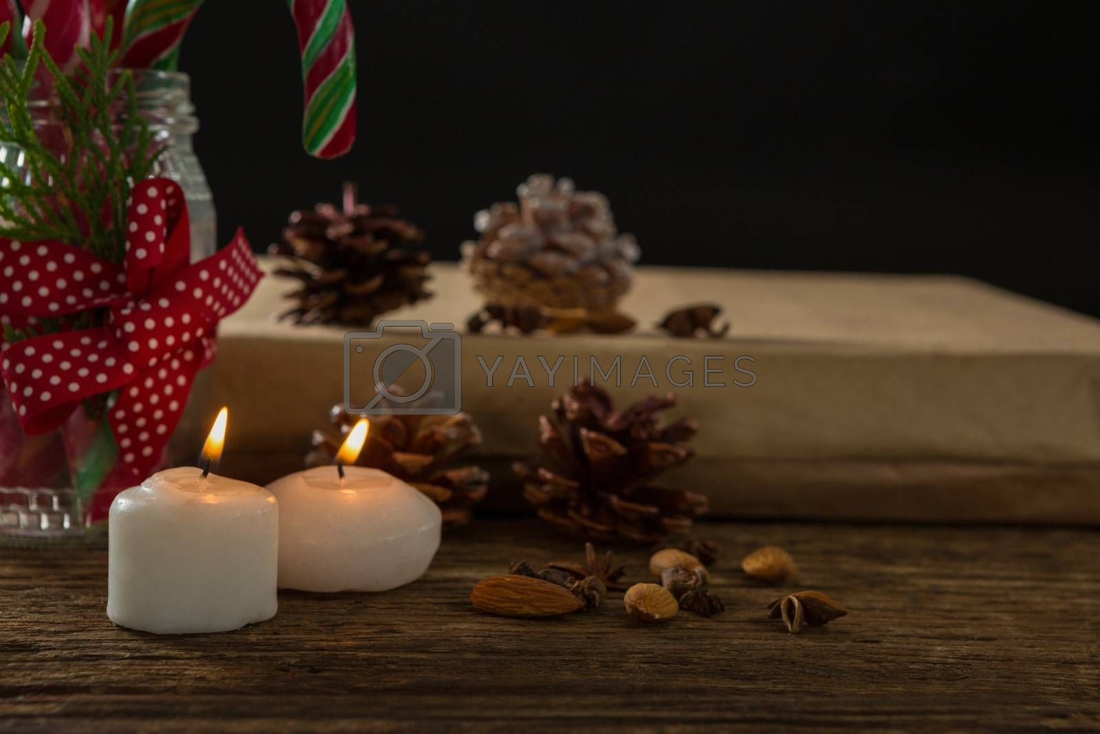 Close up of illuminated candles with pine cones and gift box by Wavebreakmedia