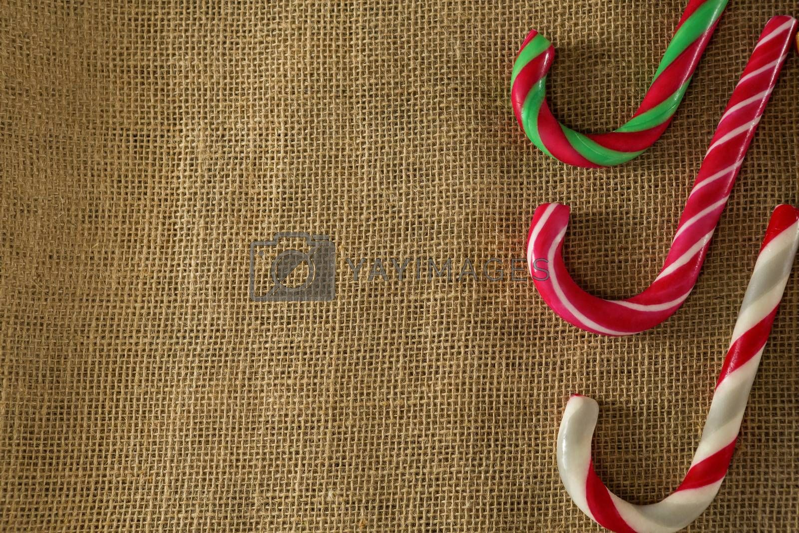 Multicolored candy canes arranged on fabric by Wavebreakmedia