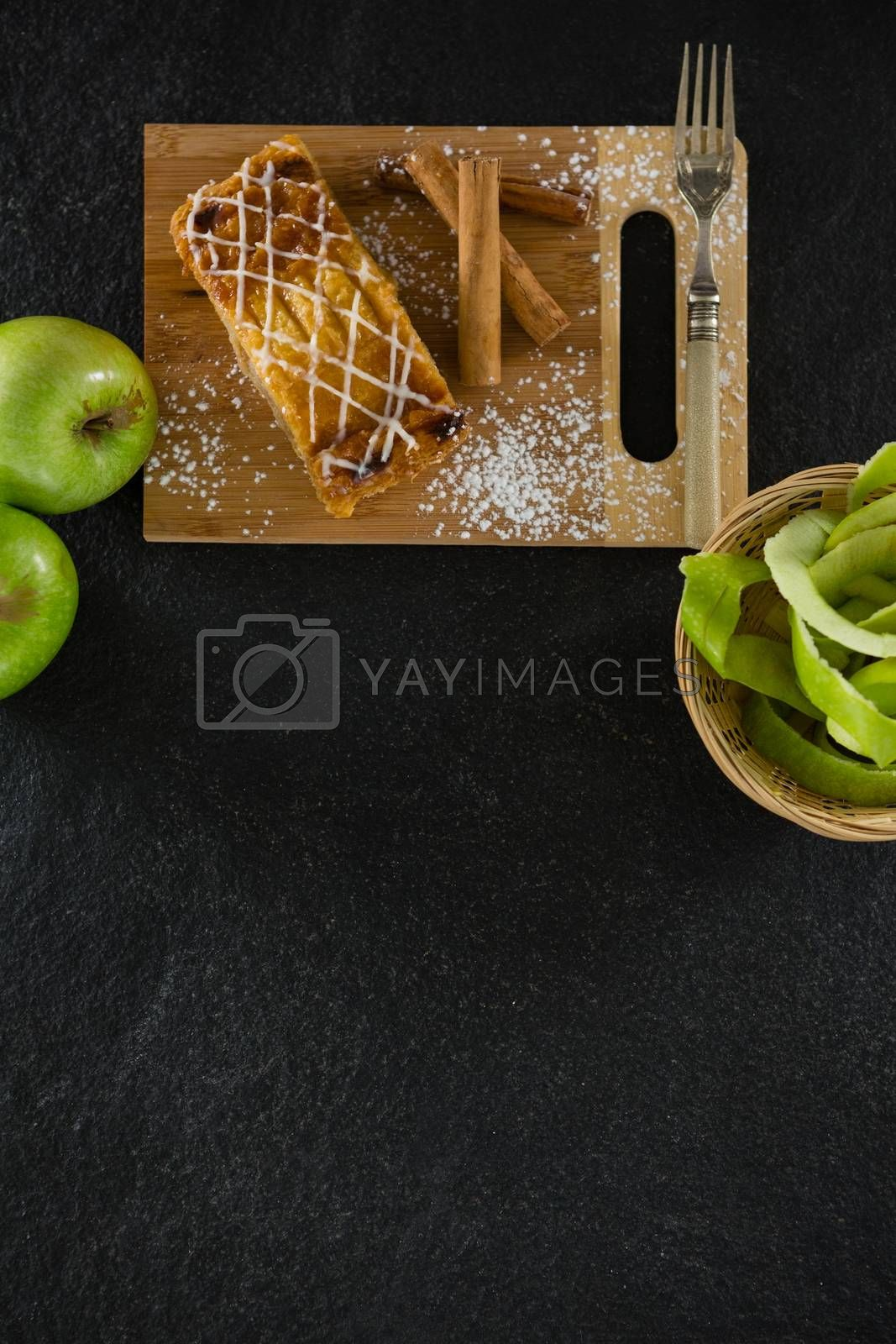 Tart and cinnamon sticks on chopping board by Wavebreakmedia