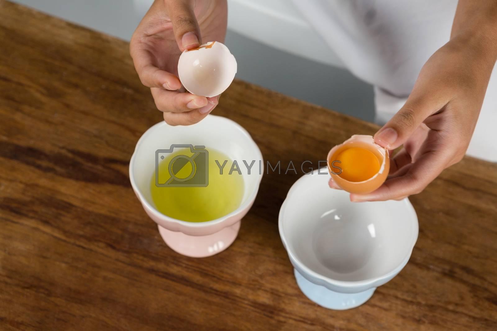 Woman holding a broken egg by Wavebreakmedia