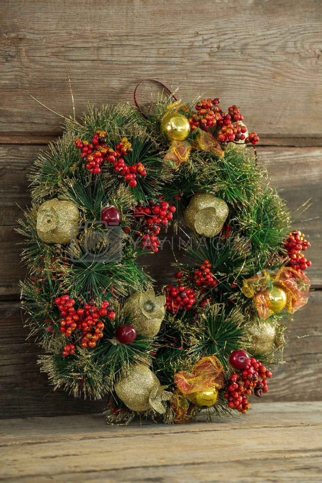 Christmas wreath against wooden background by Wavebreakmedia
