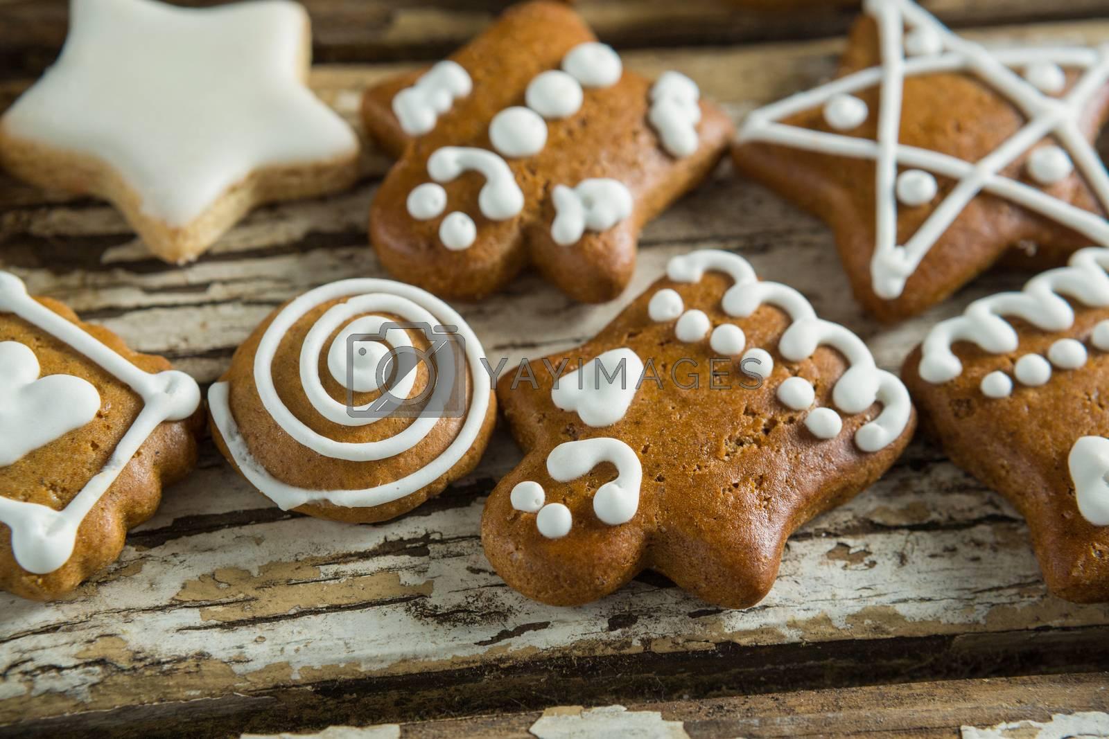 Gingerbread cookies arranged on wooden plank by Wavebreakmedia