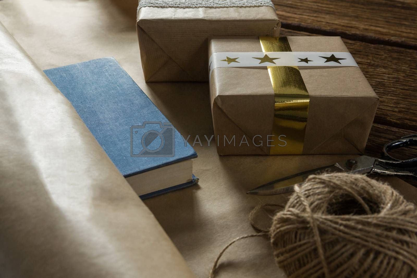 Close up of paper with gift box by scissor and thread spool by Wavebreakmedia