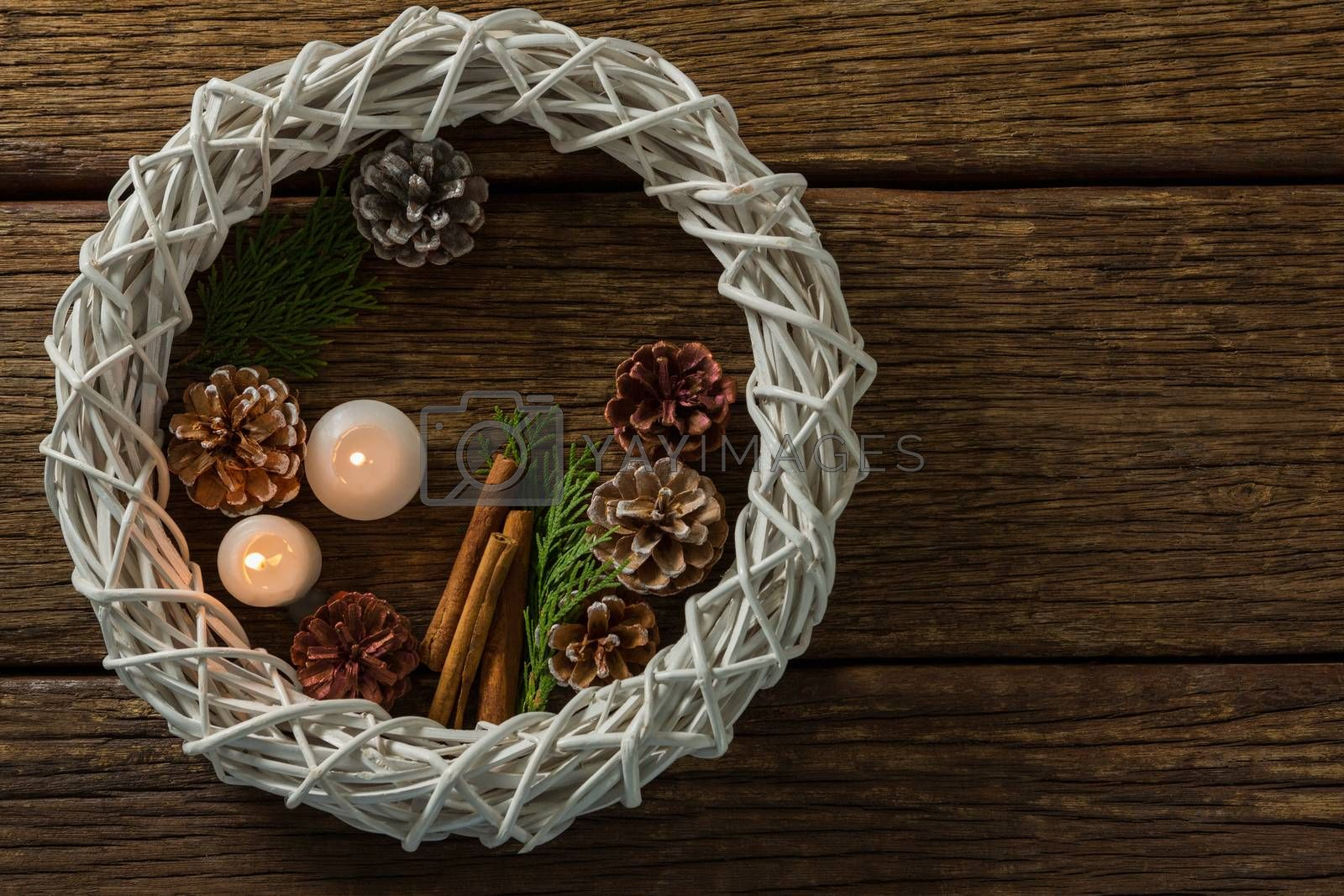 Overhead view of pine cones with illuminated candles and wreath by Wavebreakmedia