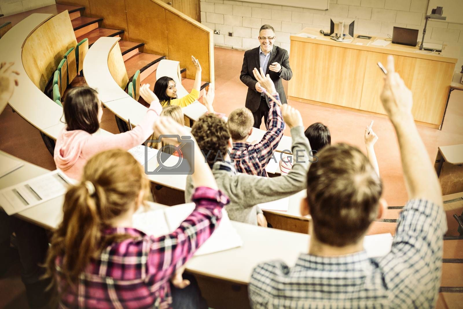 Students raising hands with teacher in lecture hall by Wavebreakmedia