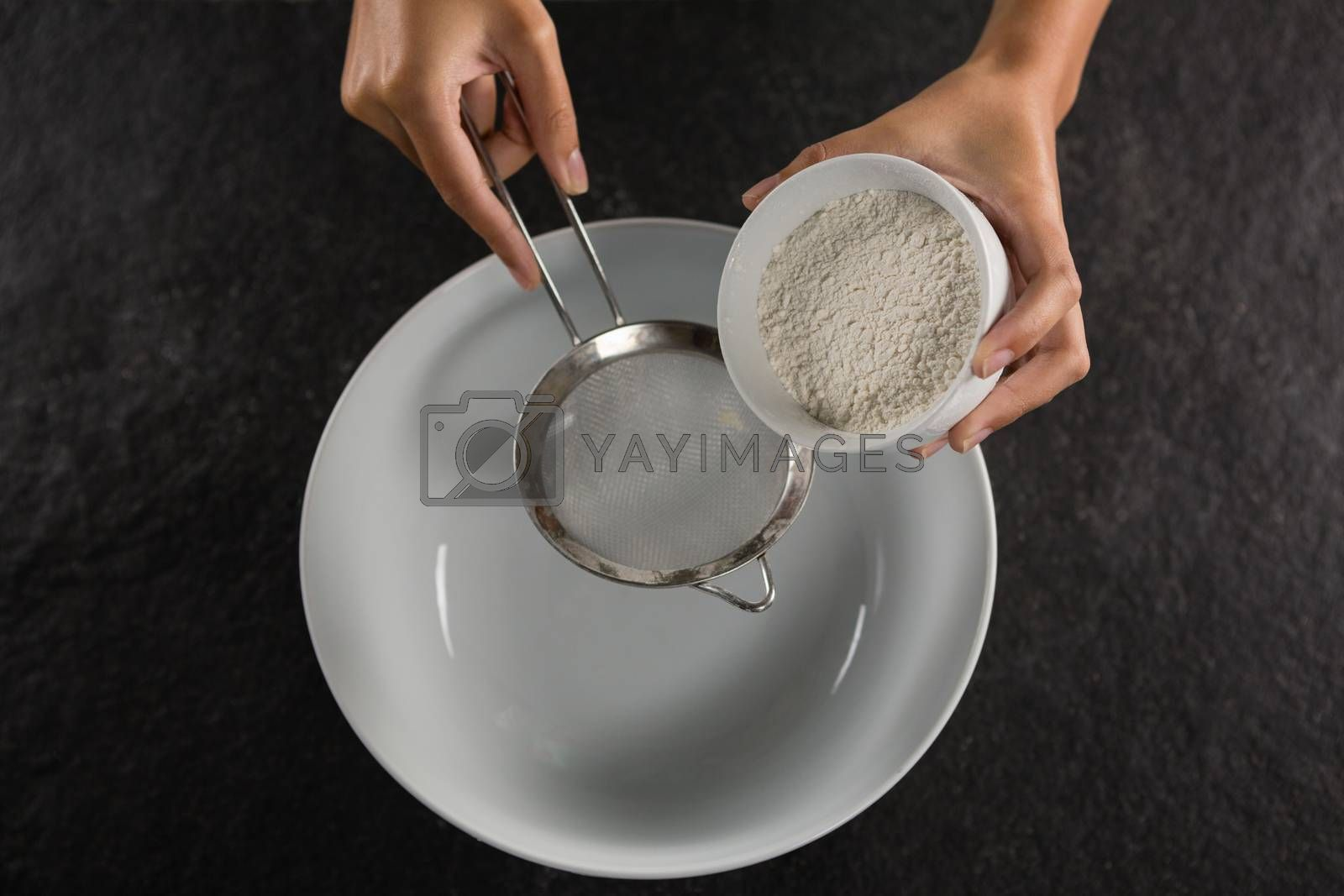 Woman sieving flour into the bowl by Wavebreakmedia