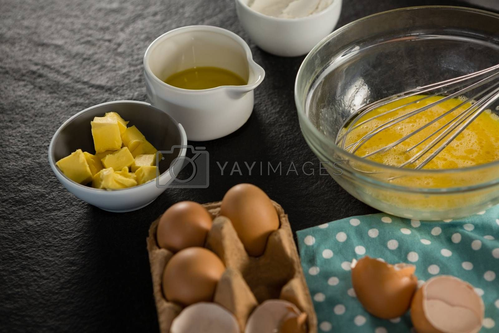 Beaten eggs, egg tray, butter, oil and flour kept on a black surface by Wavebreakmedia