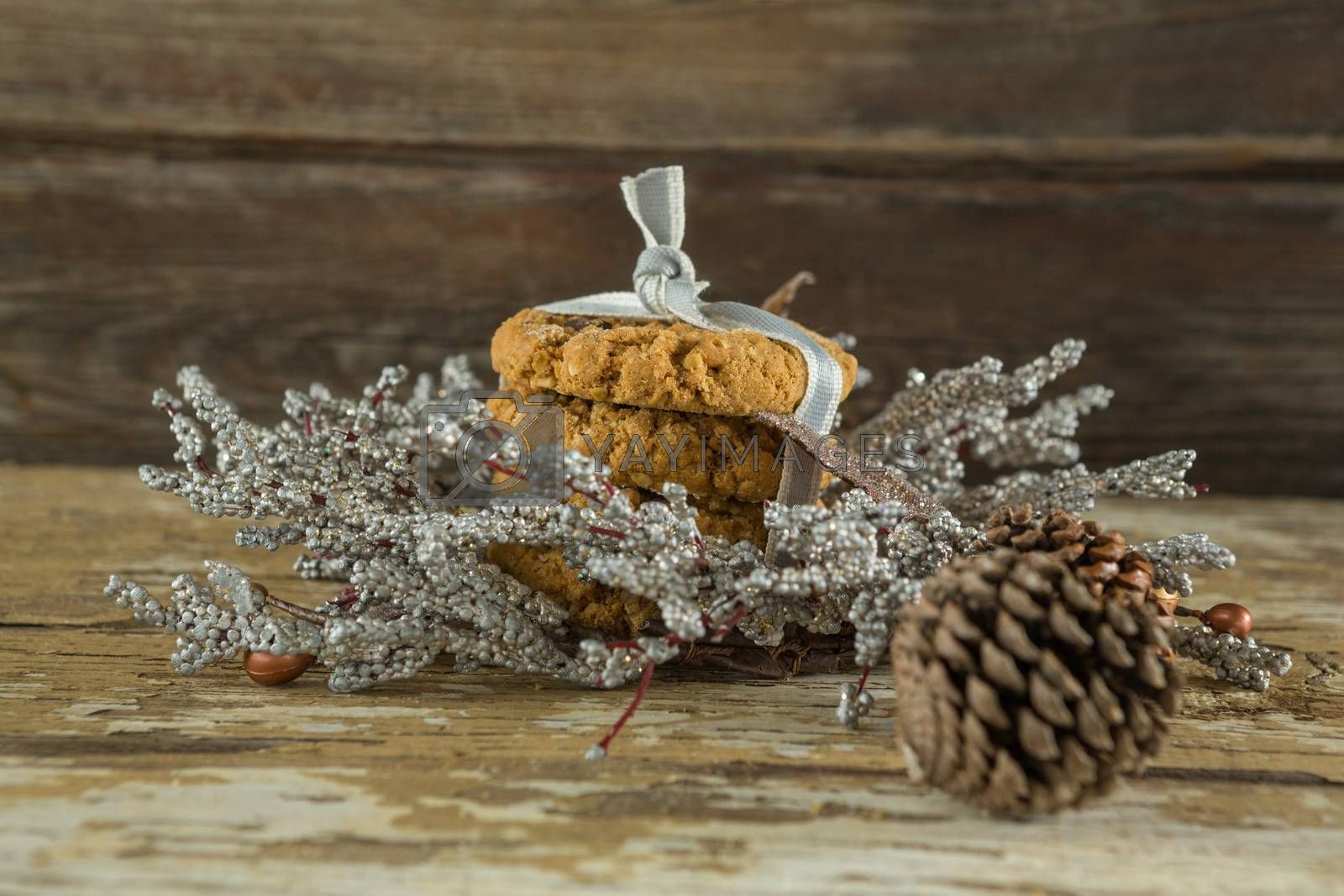 Cookies with christmas decoration arranged on wooden plank by Wavebreakmedia