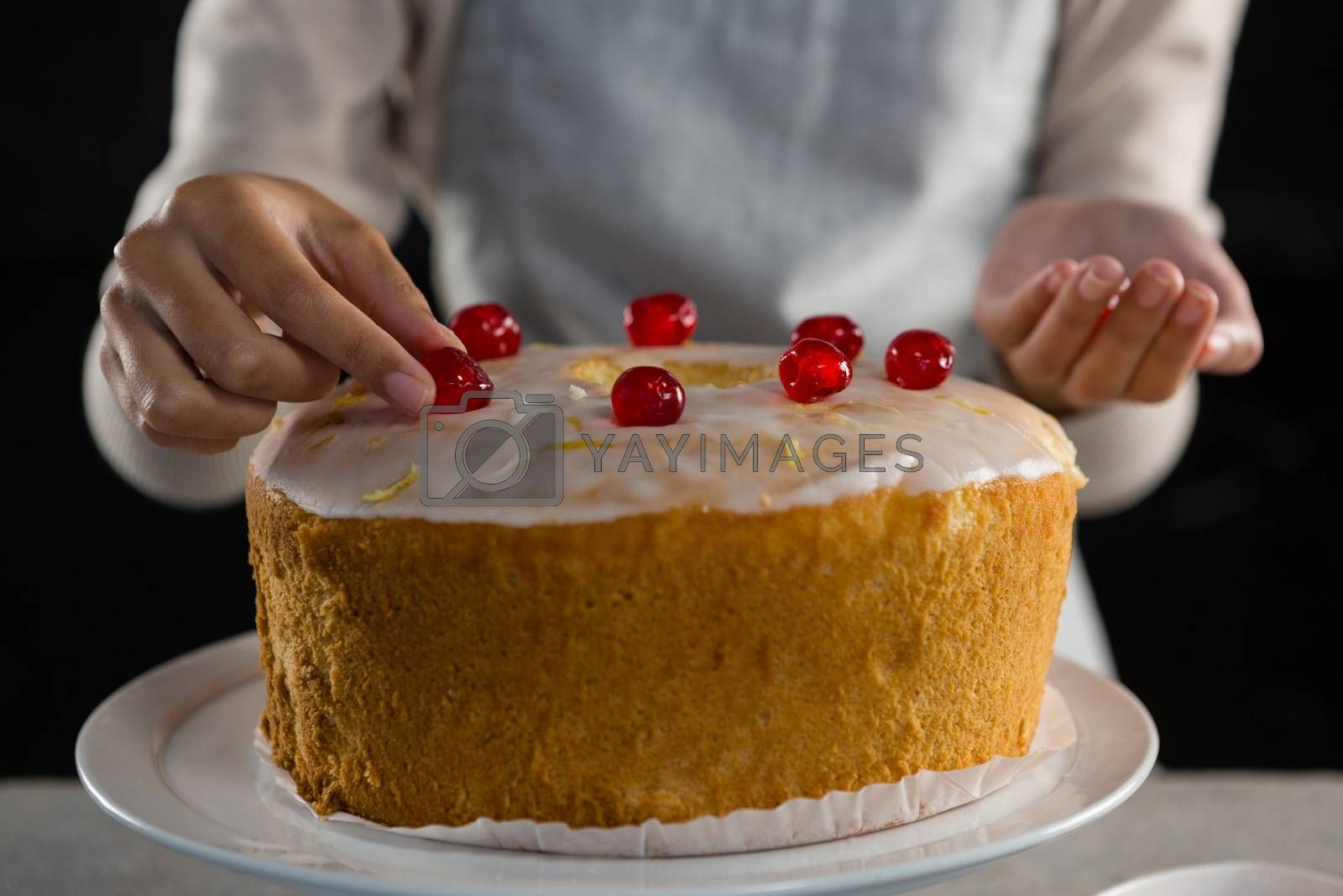 Woman toping a fresh baked cake with cherry by Wavebreakmedia