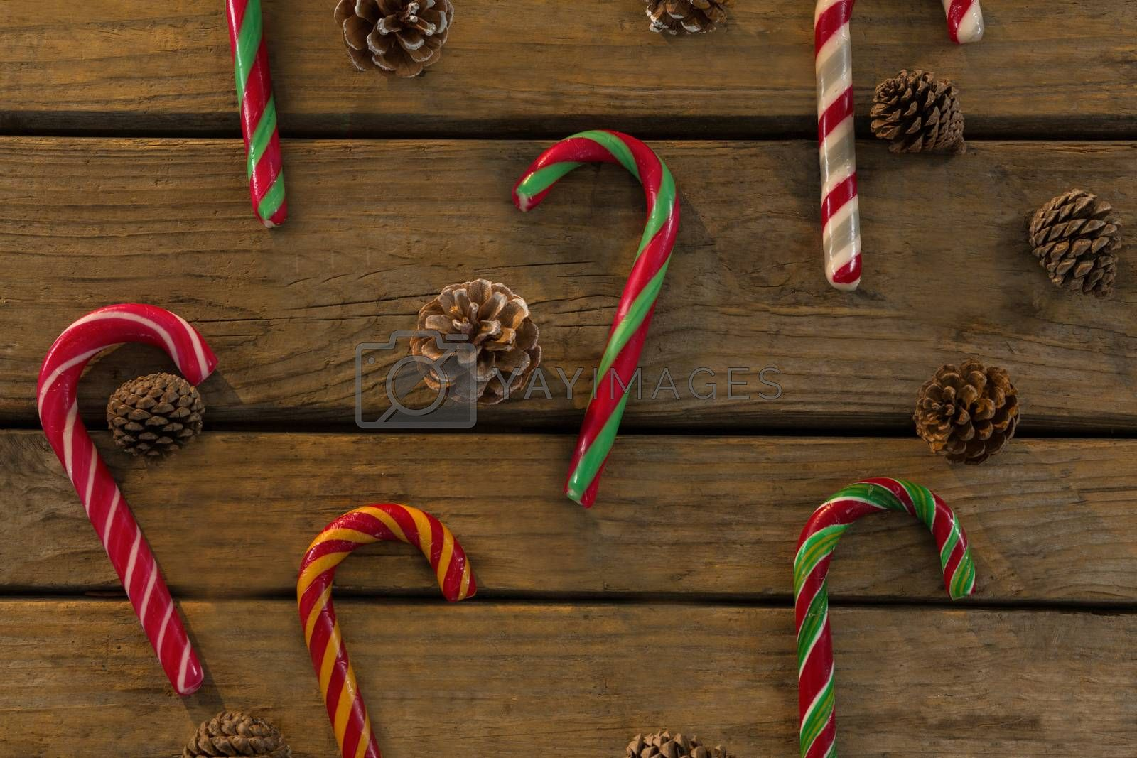 Overhead view of candy canes and pine cones on table by Wavebreakmedia