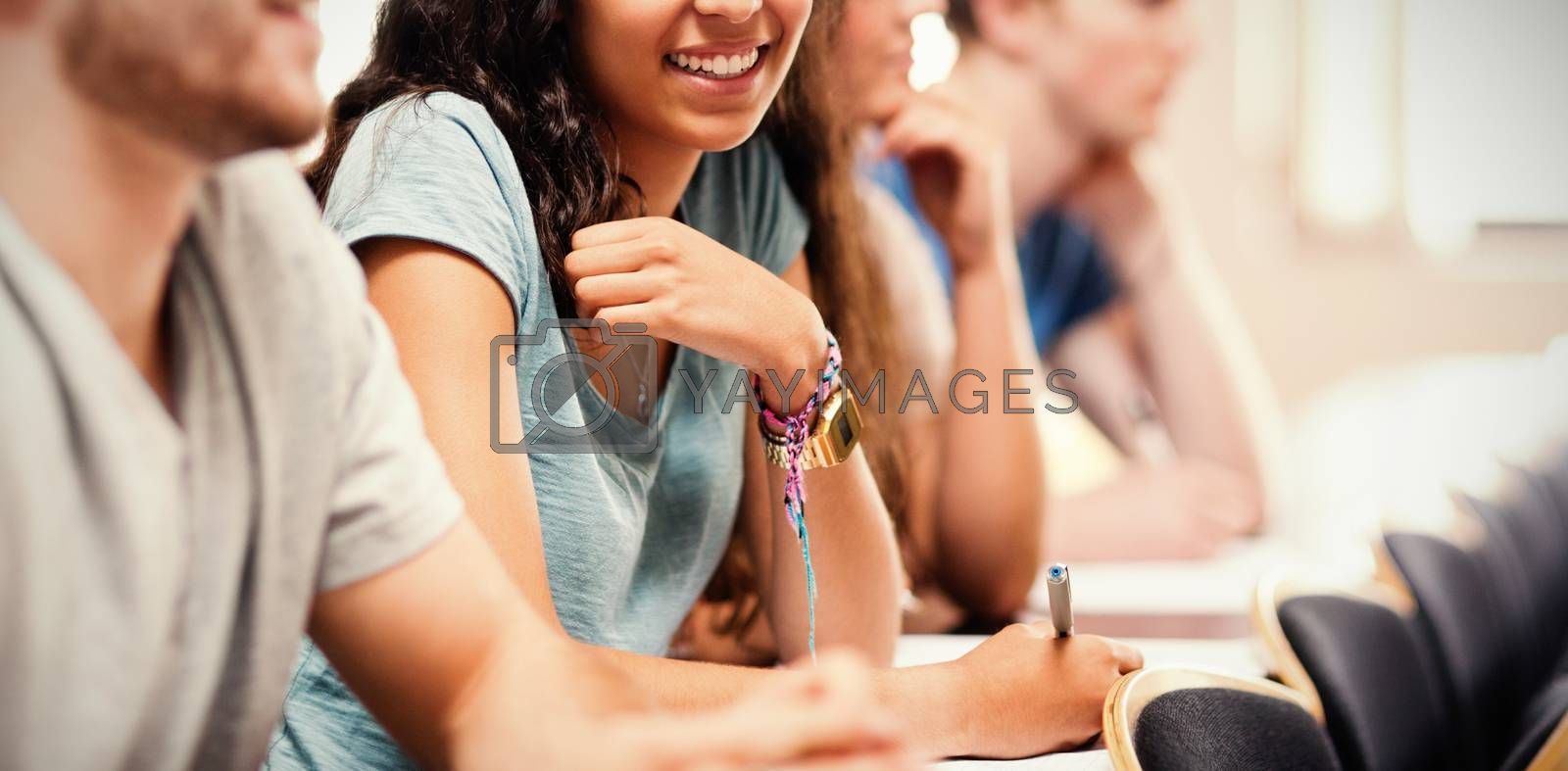 Smiling students listening lecturer by Wavebreakmedia