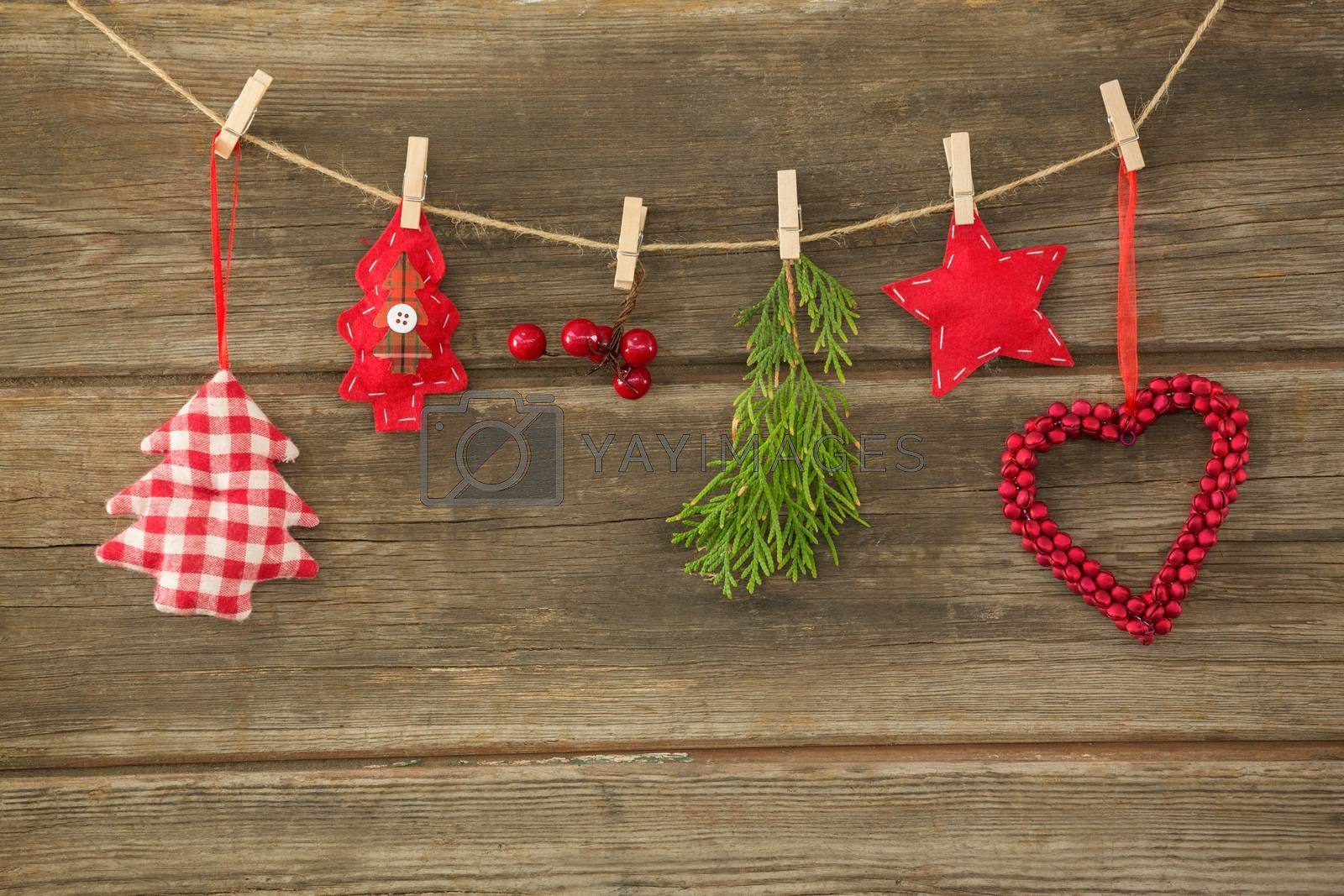 Christmas decorations hanging against wooden wall by Wavebreakmedia