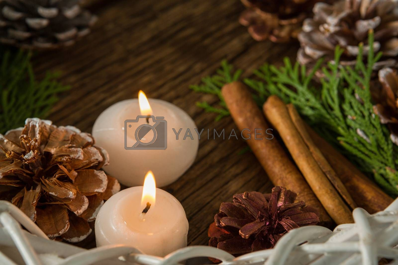 High angle view of pine cones with illuminated candles and wreath by Wavebreakmedia