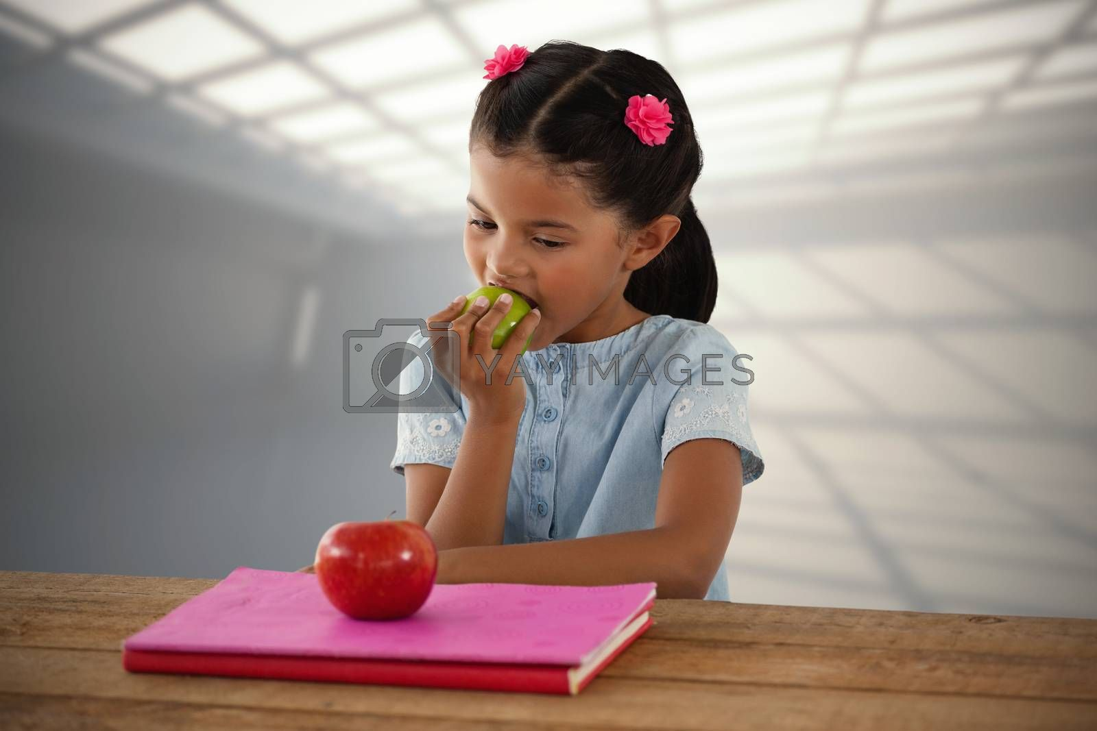 Composite image of girl eating granny smith apple at table by Wavebreakmedia