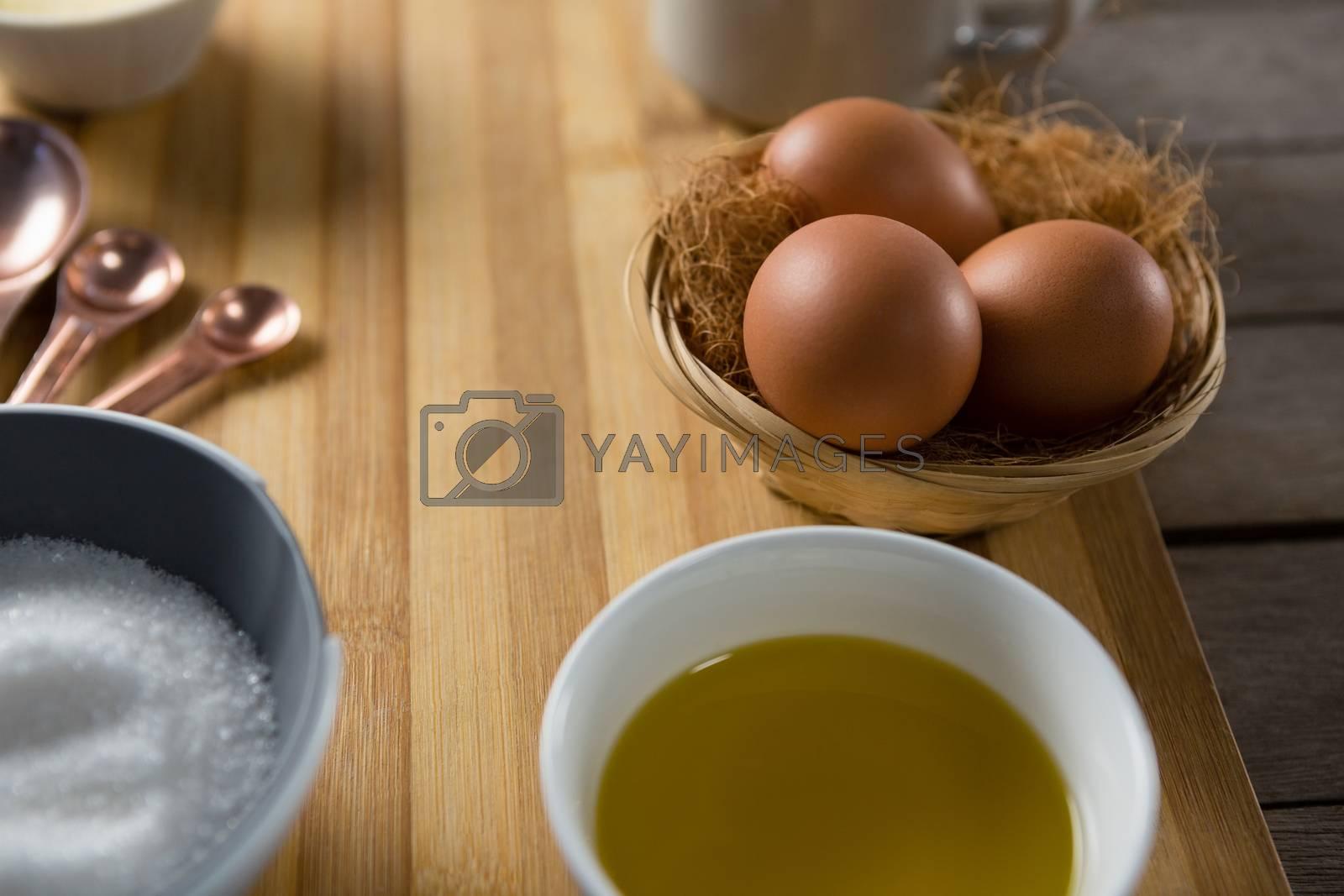 Eggs in wicker basket with oil, and sugar on wooden board by Wavebreakmedia
