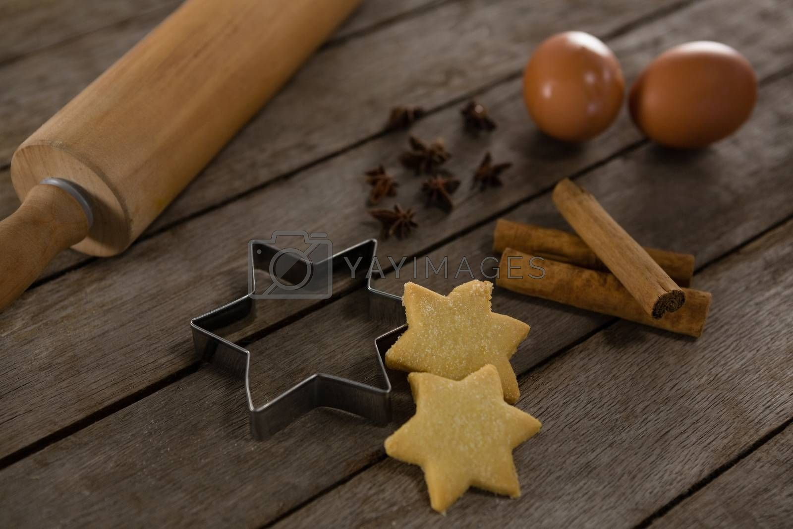 Rolling pin with eggs, cookie cutter, cookies, cinnamon and anise by Wavebreakmedia