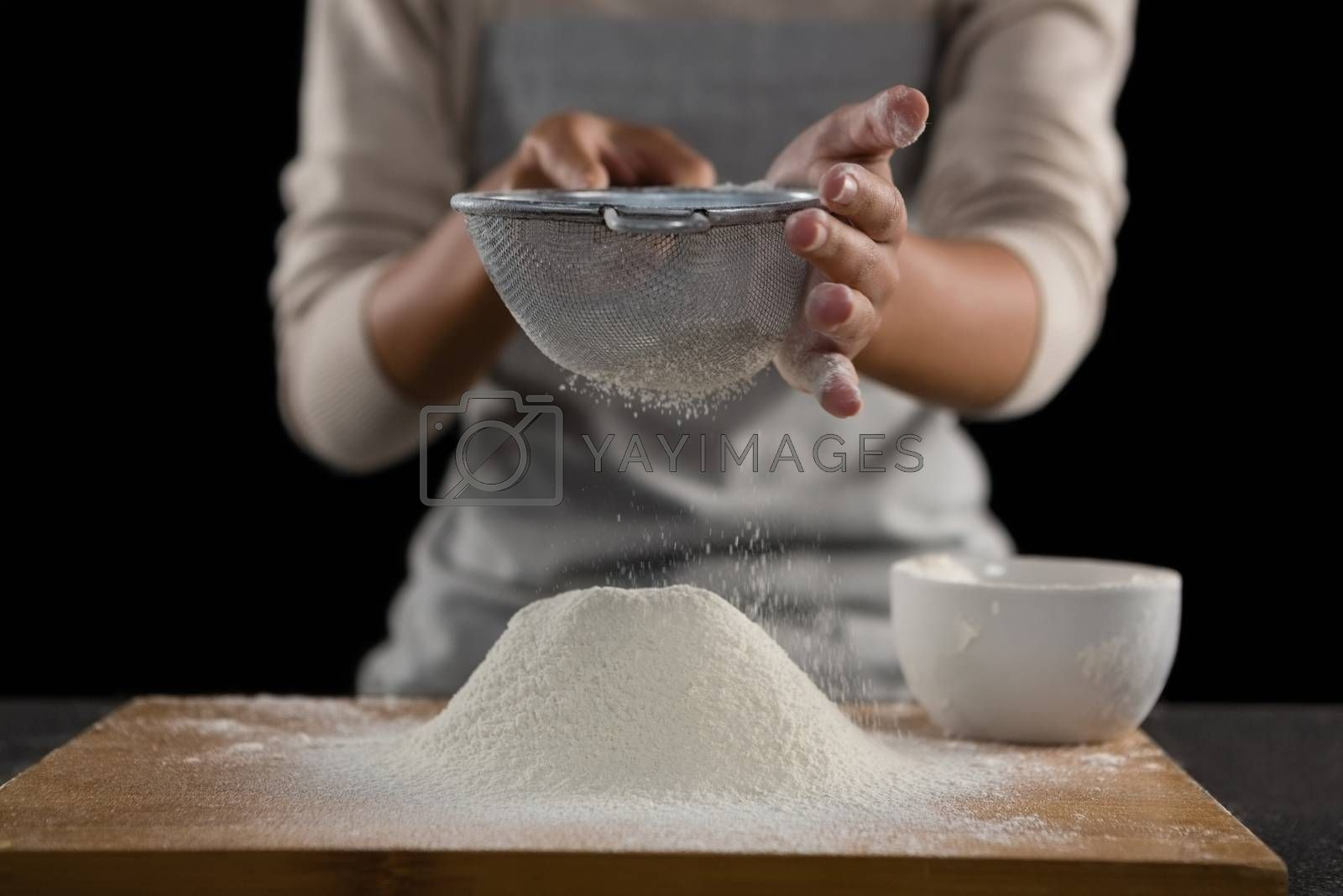 Woman sieving flour from the bowl on the wooden board by Wavebreakmedia